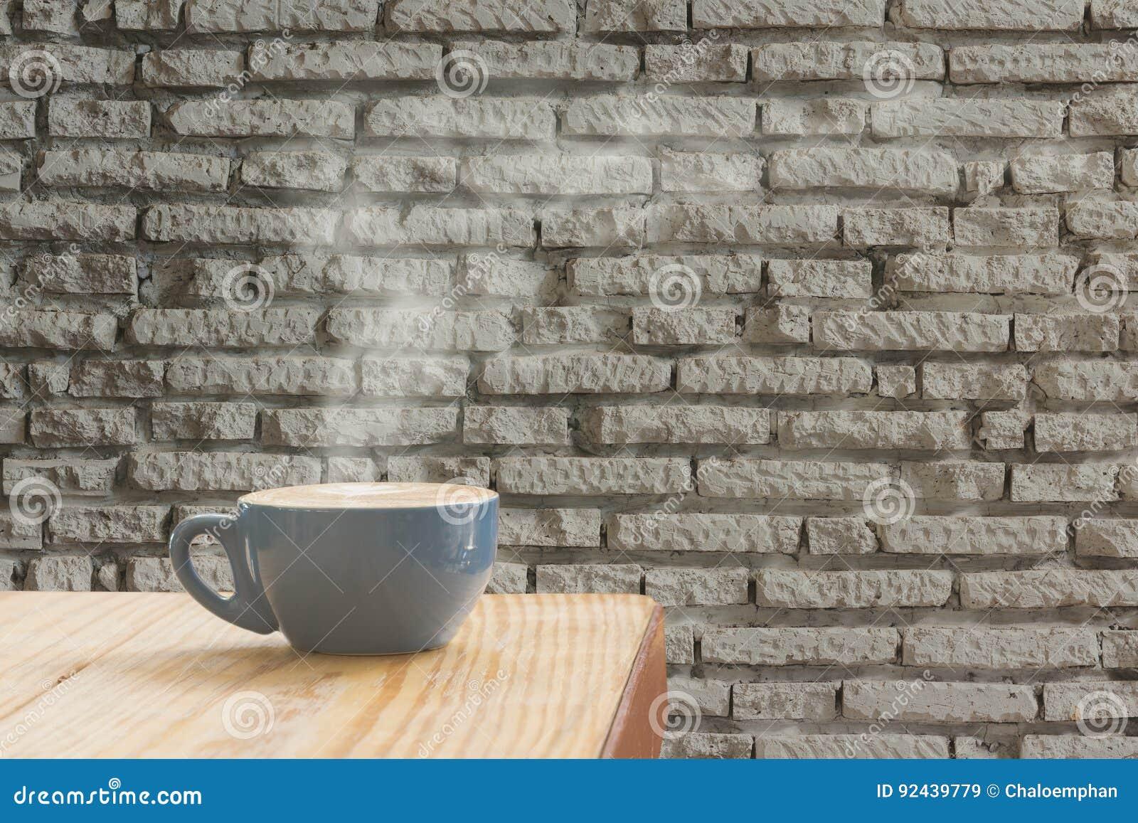 Tasse de café avec le courant de la vapeur contre le backgr blanc de mur de briques