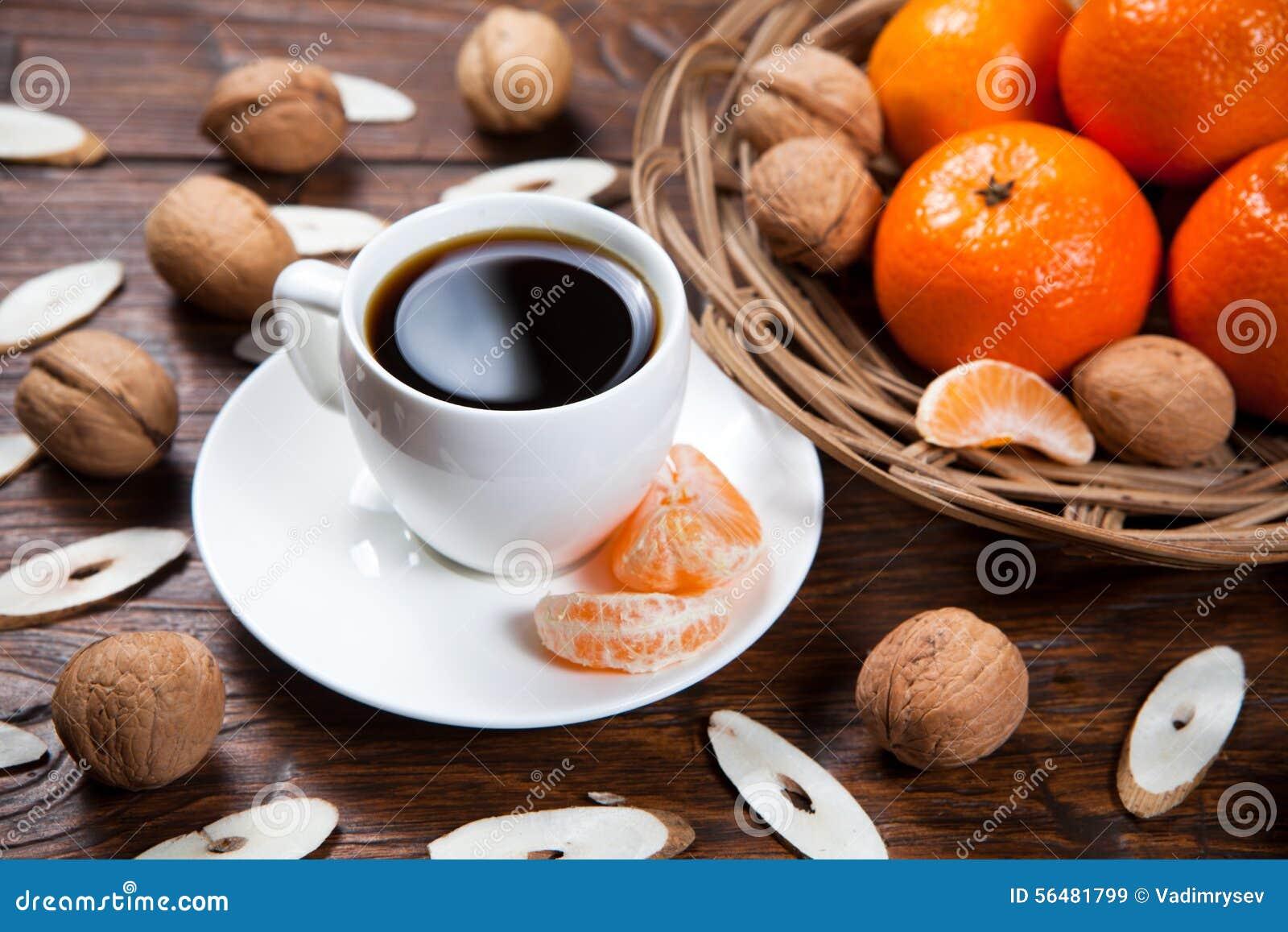 Tasse de café avec les mandarines et la noix