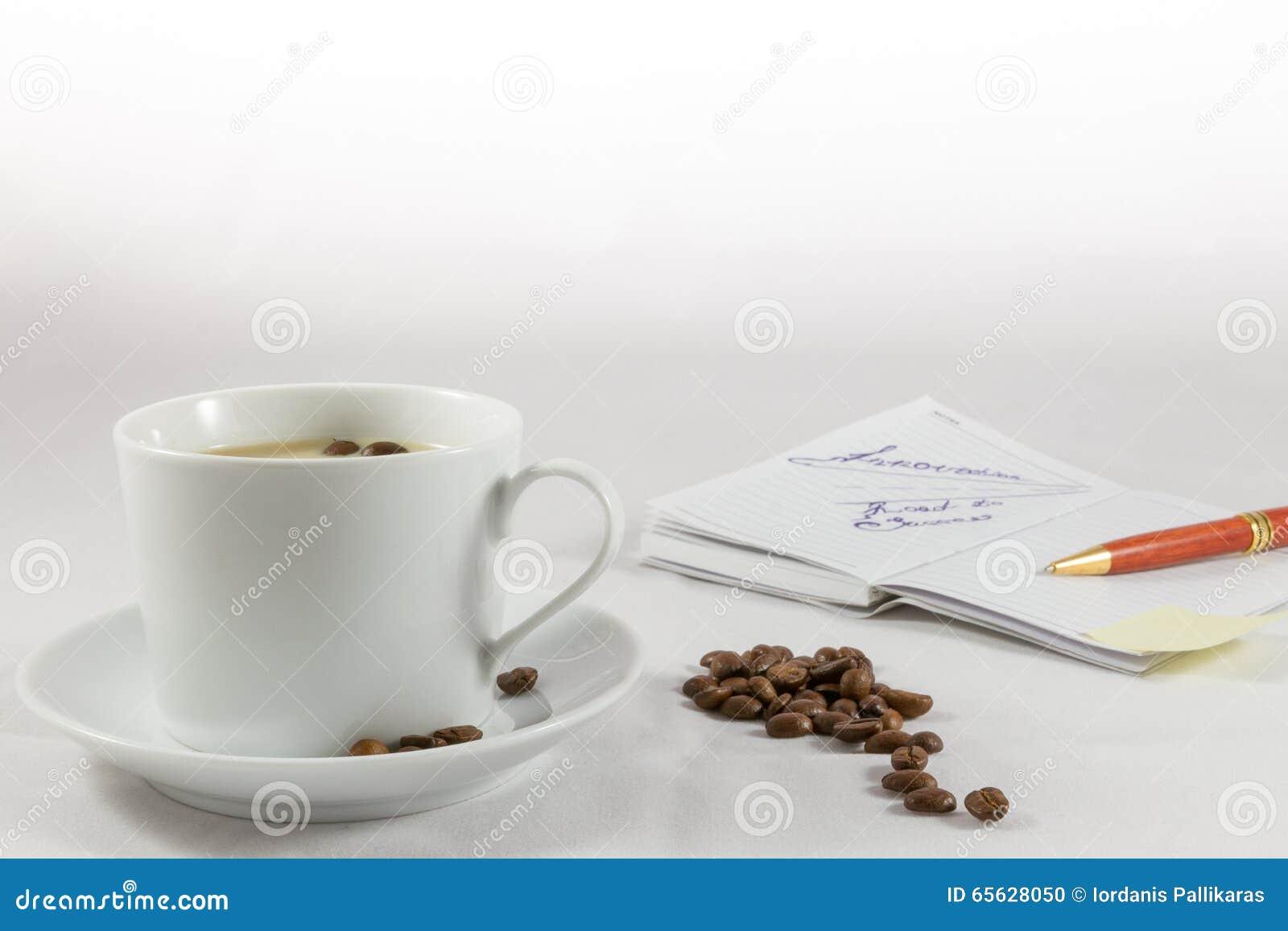 Tasse de café, carnet, stylo et grains de café sur le fond blanc