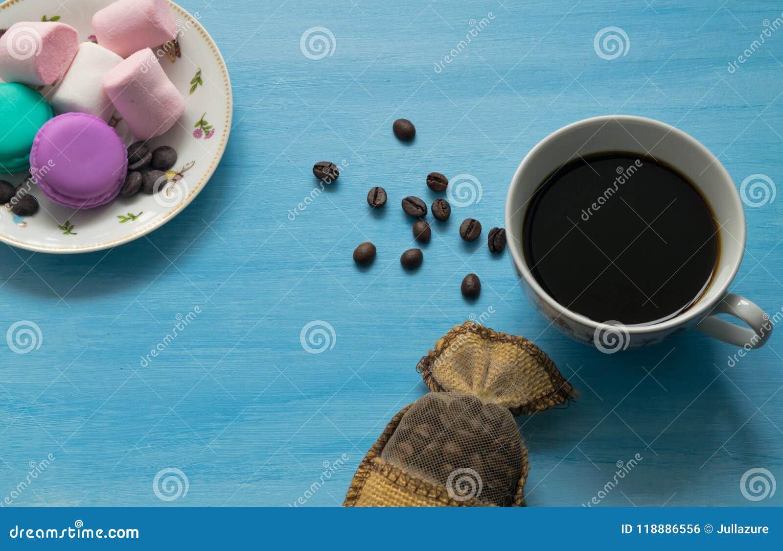Tasse de café chaud avec des guimauves et des macarons sur le fond bleu