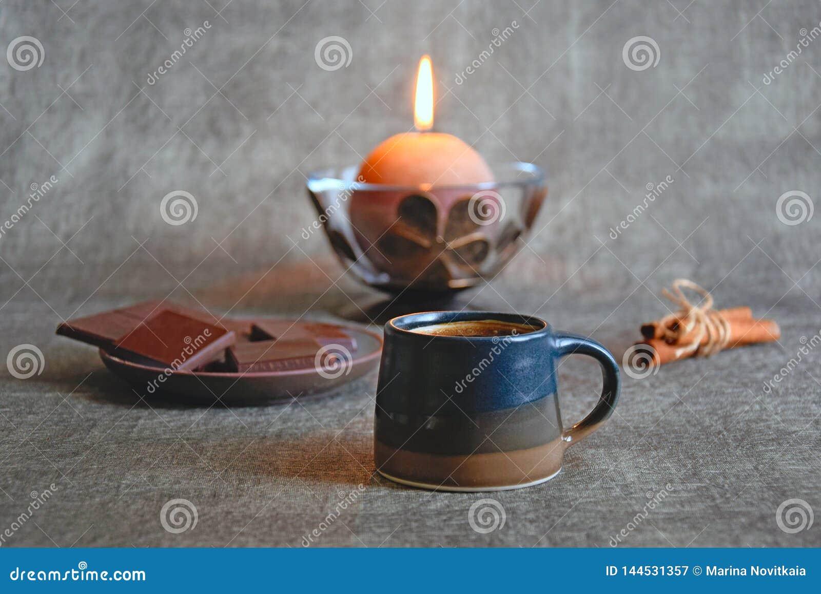 Tasse de café, de chocolat foncé, des bâtons de cannelle et de la bougie décorative brûlante