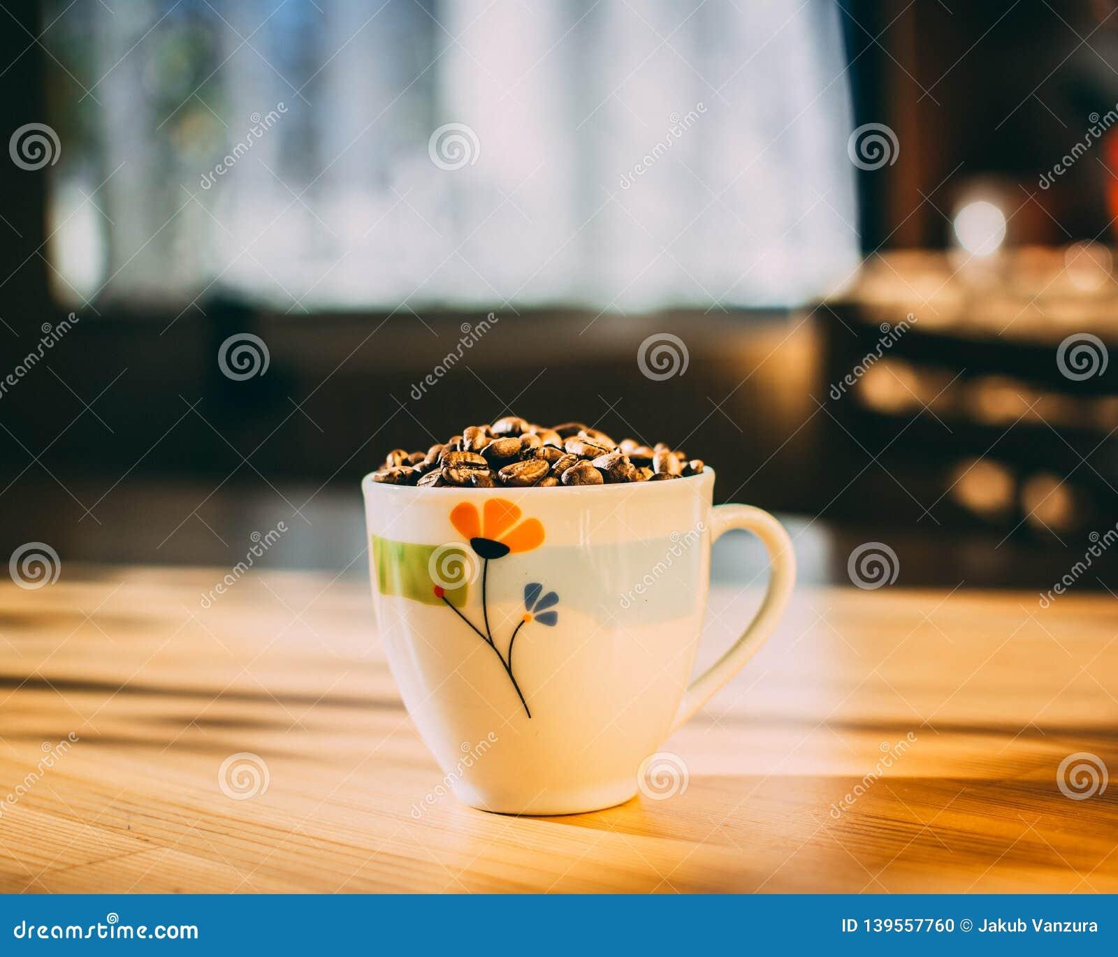 Tasse de café complètement de grains de café rôtis