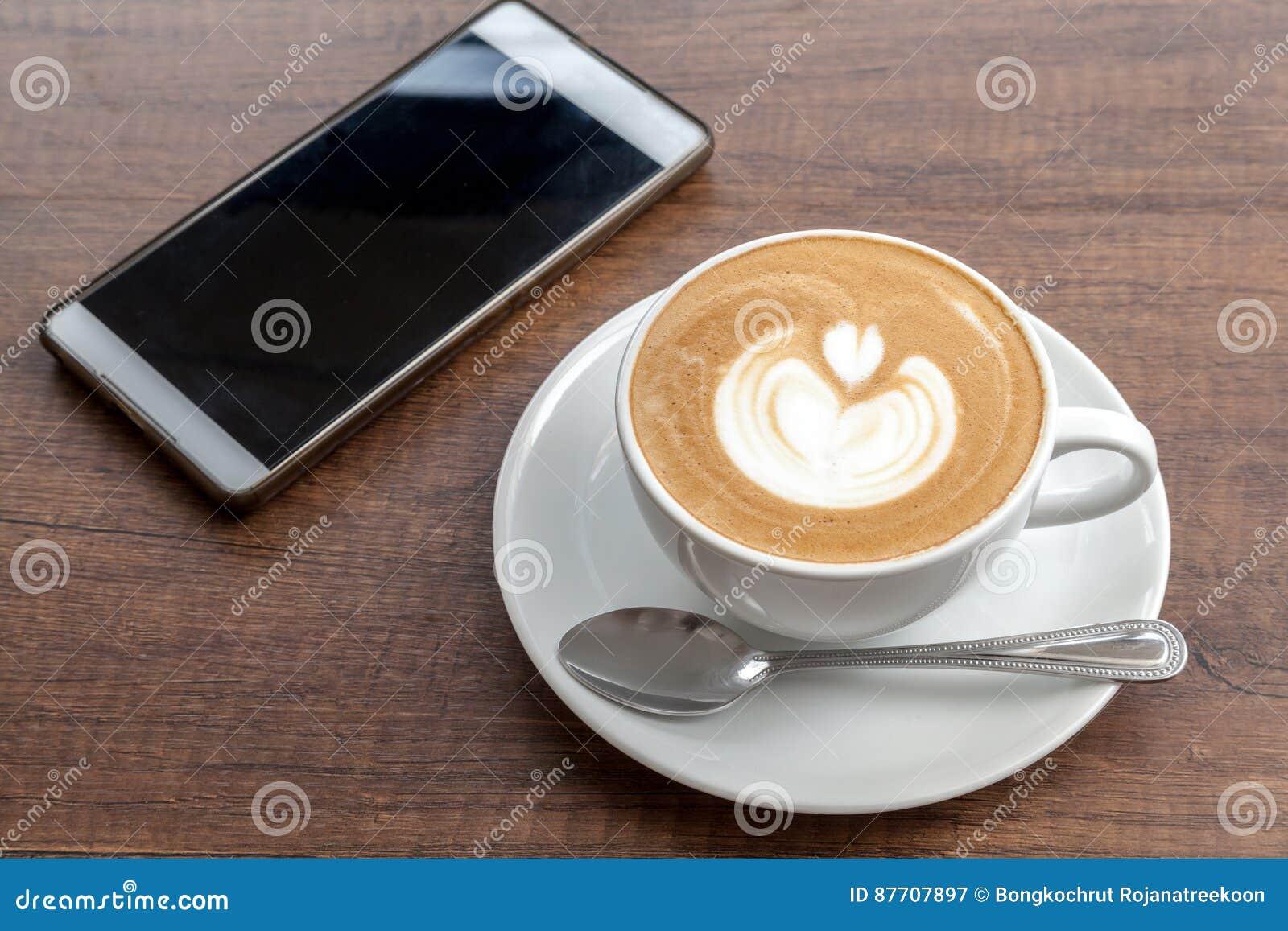 Tasse de café d art de latte avec le smartphone sur le fond en bois