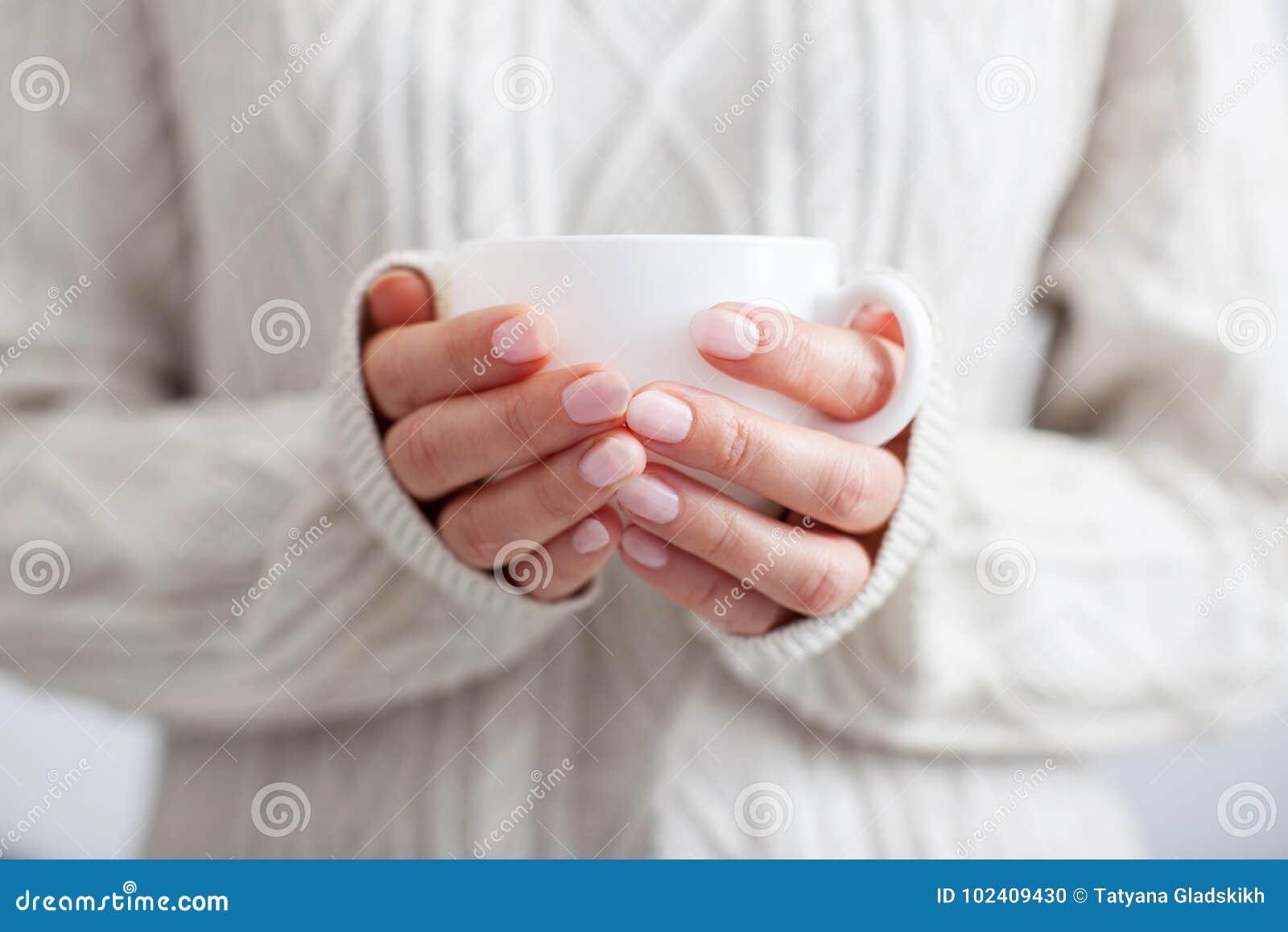 Tasse de café dans des mains femelles