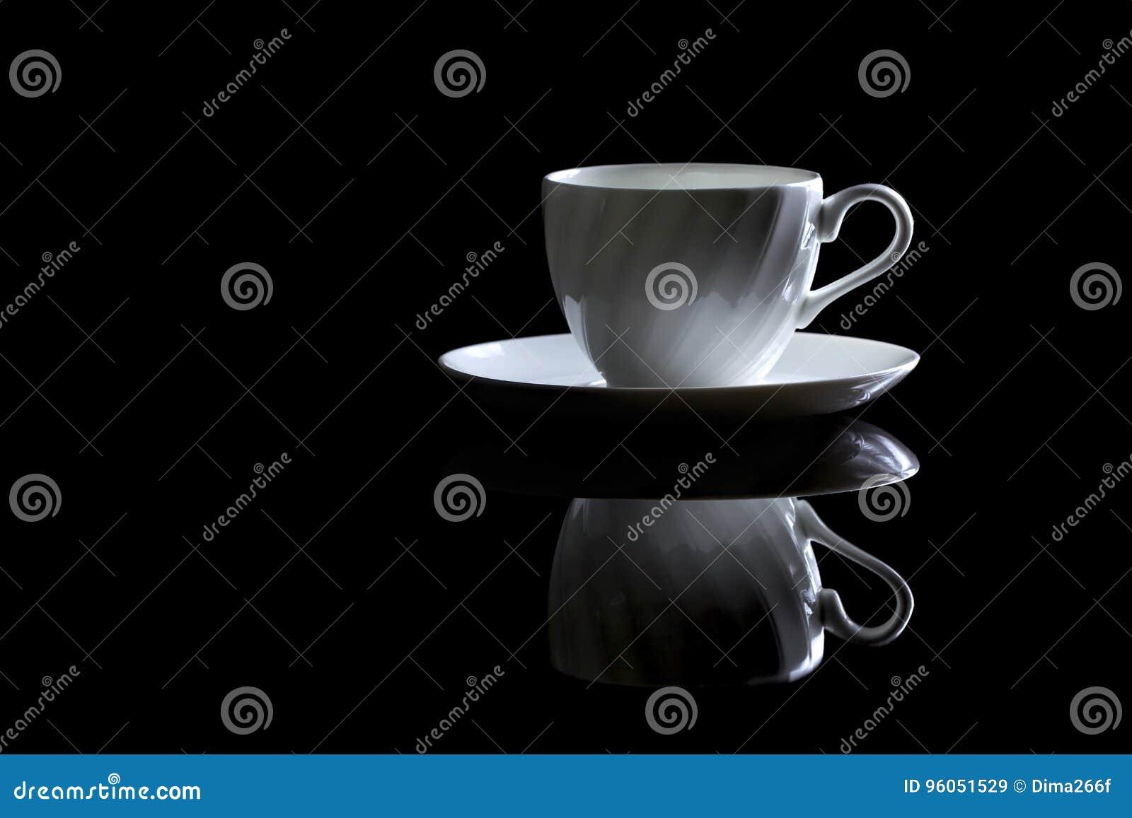 Tasse de café dans le contre-jour sur un fond réfléchi noir