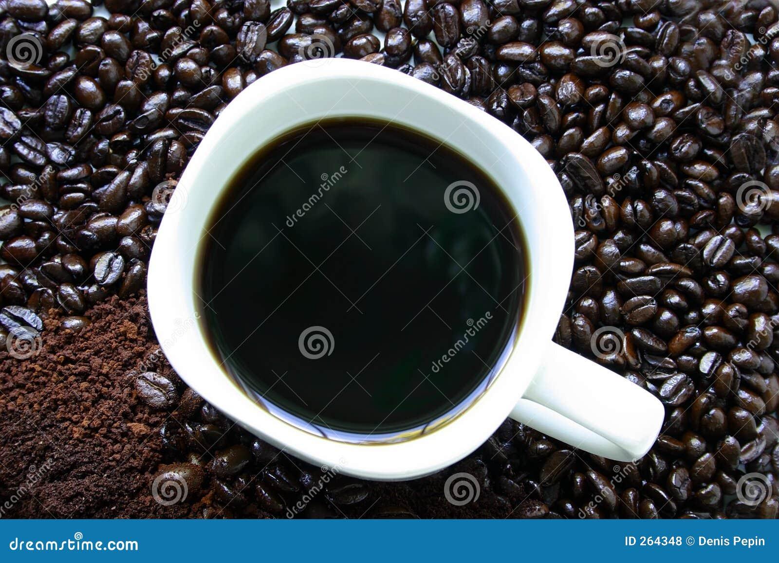 Tasse de café entourée par des grains de café