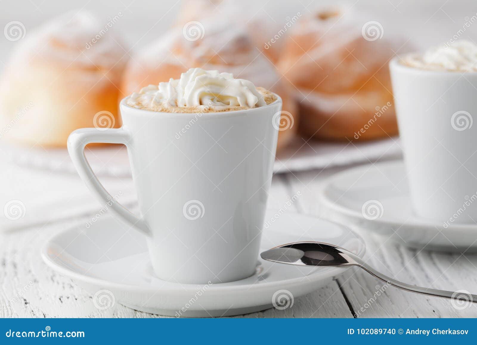 Tasse de café noir et de petit pain doux pour le petit déjeuner, plan rapproché
