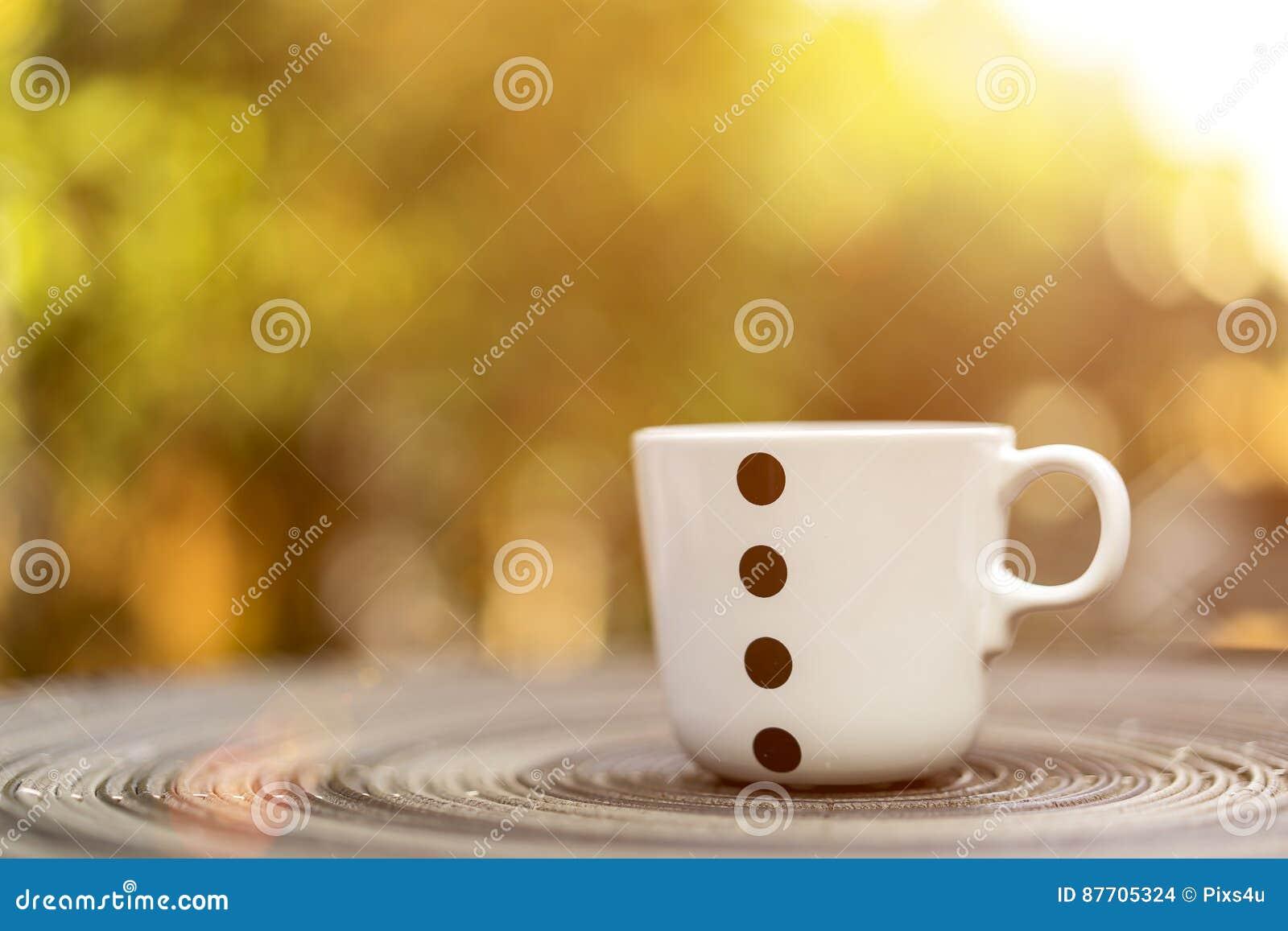 Tasse de café ou de thé sur la table et le fond vert de bokeh