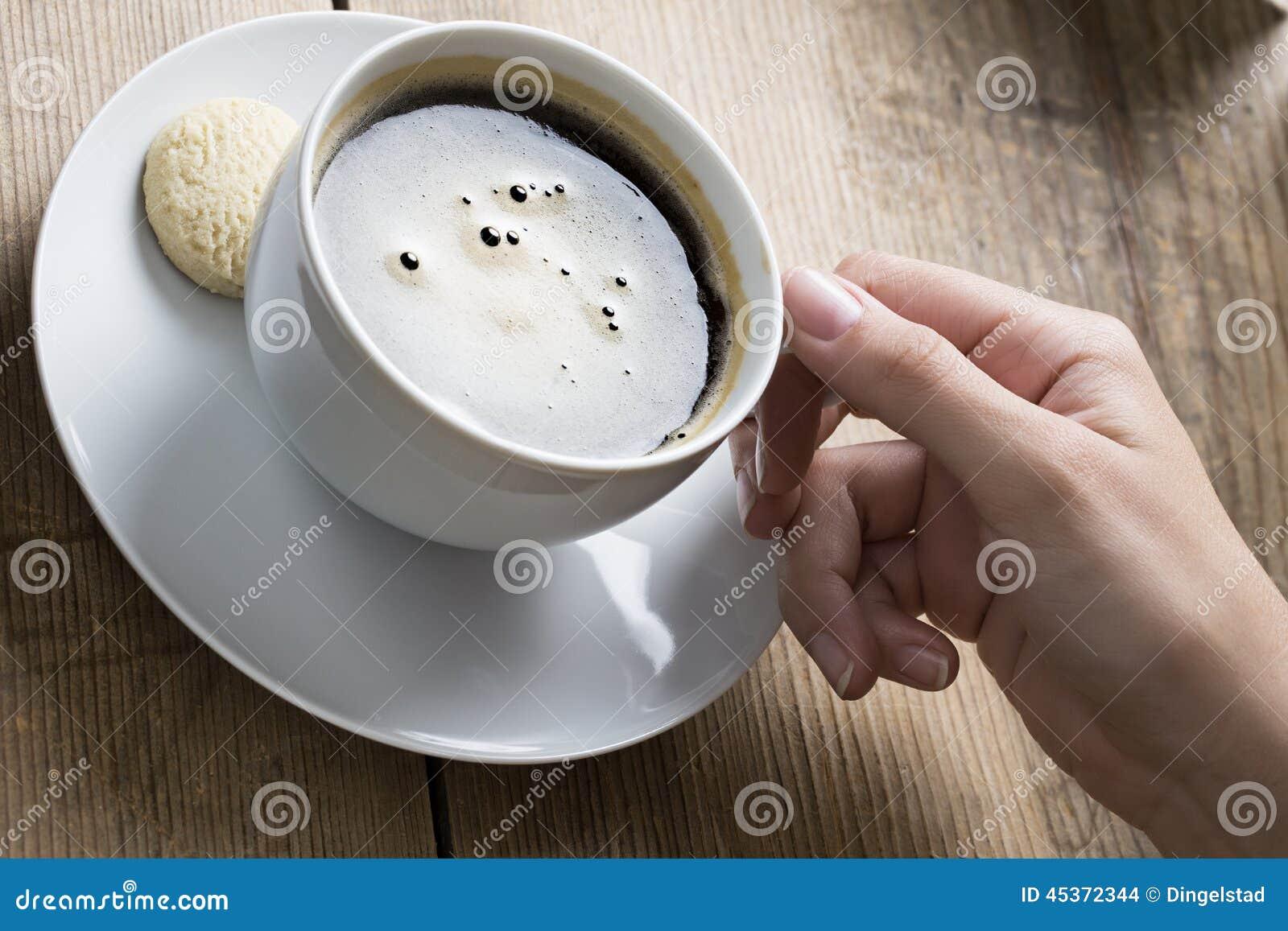 Tasse de café tenu par une main humaine blanche