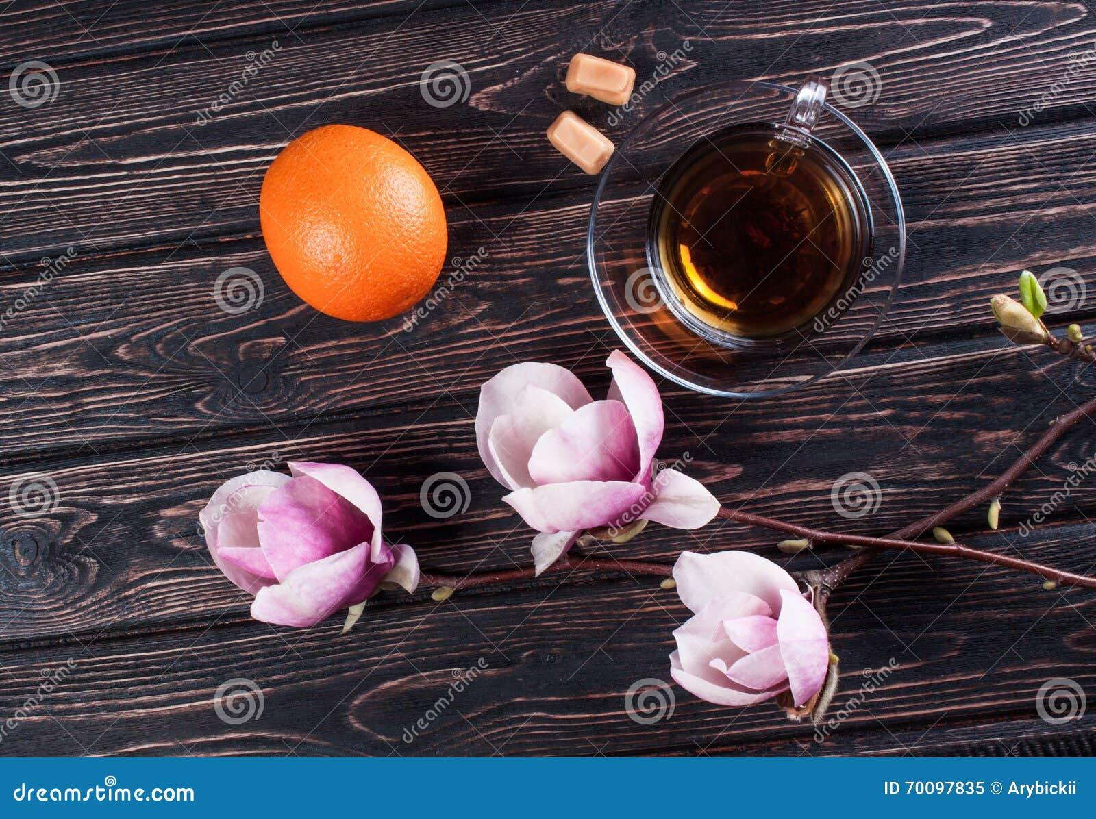 Tasse de magnolia de thé noir et de fleur avec l orange sur les conseils en  bois Composition avec la fleur de magnolia 1a6483da890