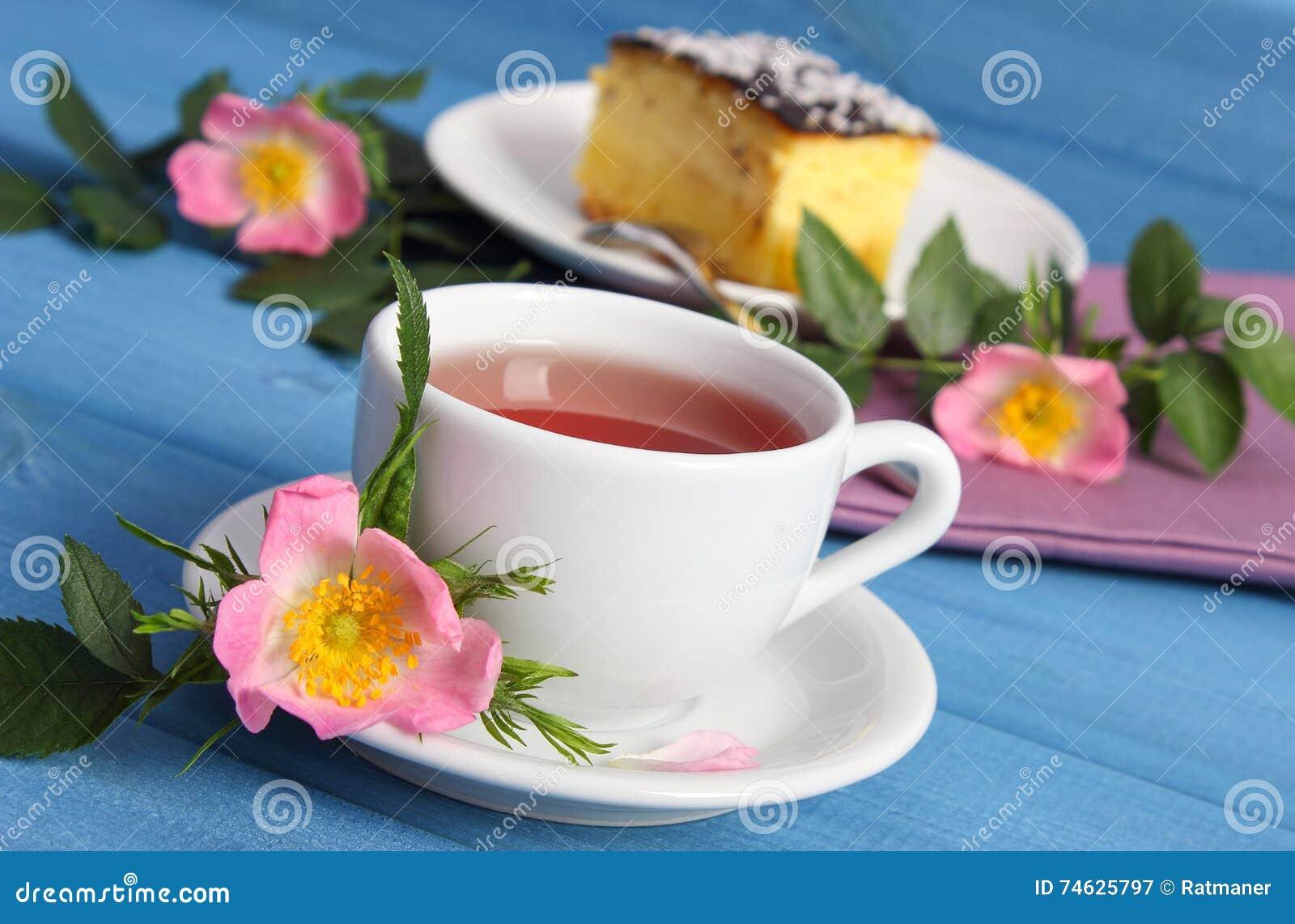 La tasse de thé chaud avec la rose sauvage et la floraison fleurit sur les  panneaux bleus, gâteau au fromage de plat à l arrière-plan 1e2a3e6c60a