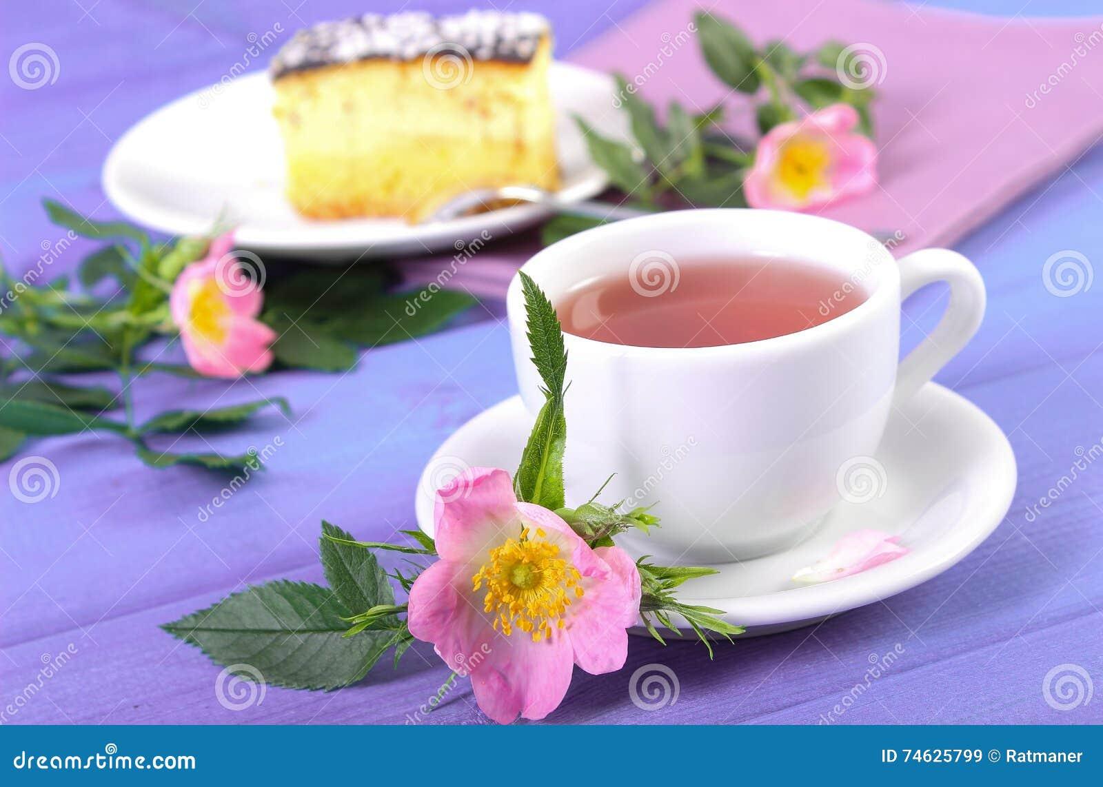 La tasse de thé chaud avec la rose sauvage et la floraison fleurit sur les  panneaux pourpres, gâteau au fromage de plat à l arrière-plan bd5a7dcc181