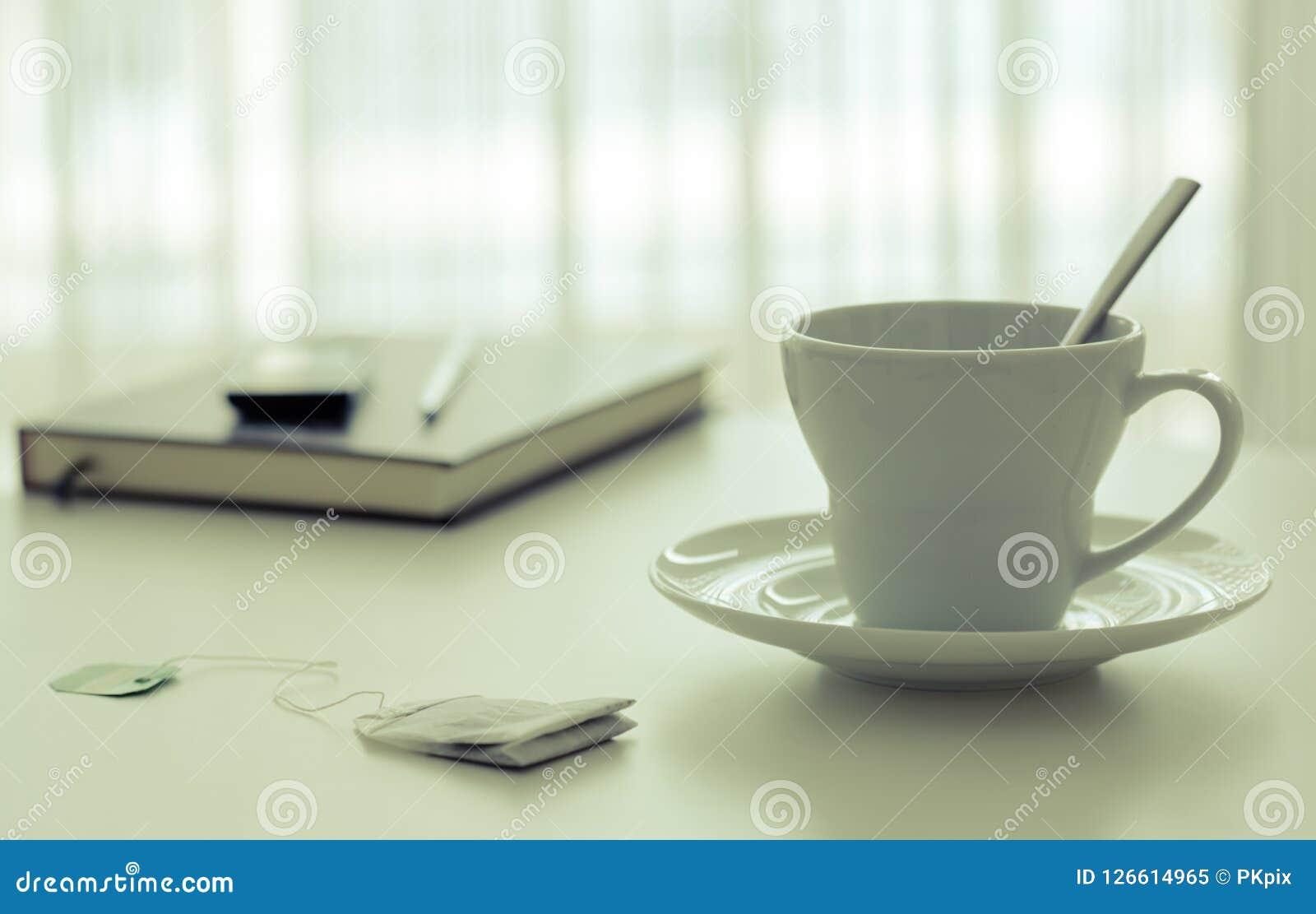 Tasse de thé près d un livre et stylo près de la fenêtre