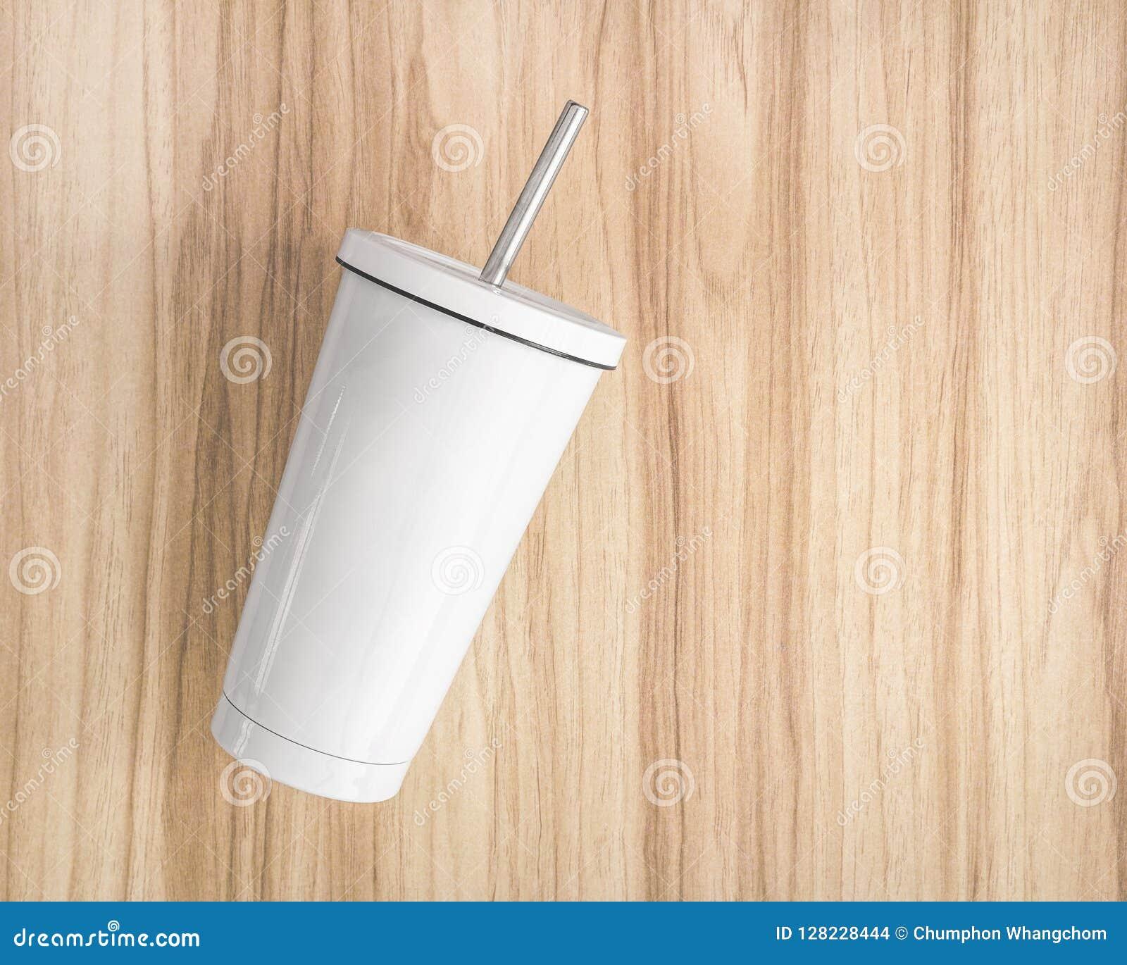 Tasse en acier blanche avec le tube sur le fond en bois Le récipient isolé pour gardent votre boisson
