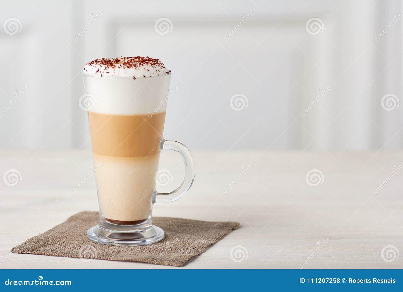 Tasse en verre de latte de café sur la table en bois