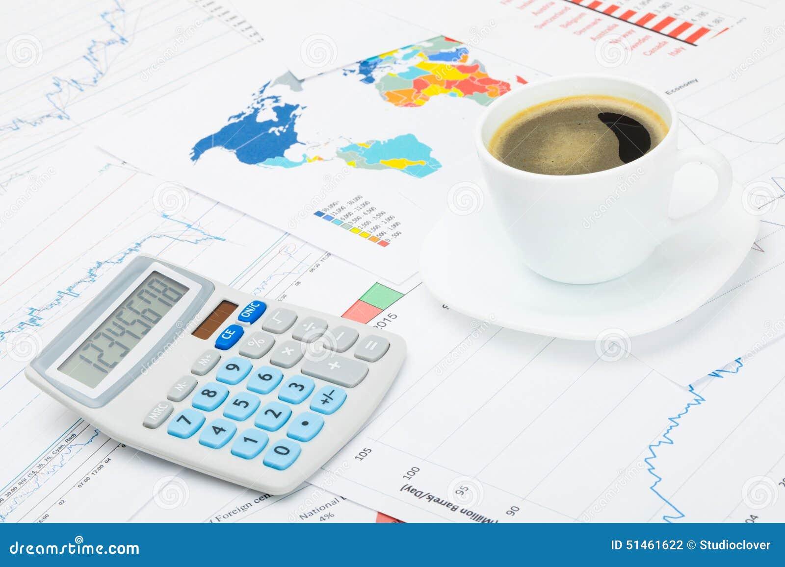 Tasse et calculatrice de café au-dessus des diagrammes financiers