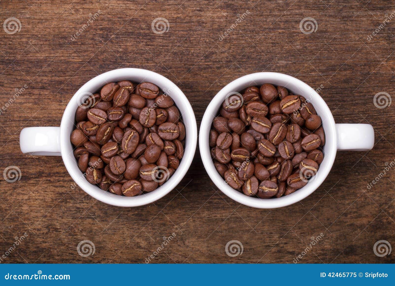 Tasse Kaffee-Bohnen auf dem braunen hölzernen Hintergrund