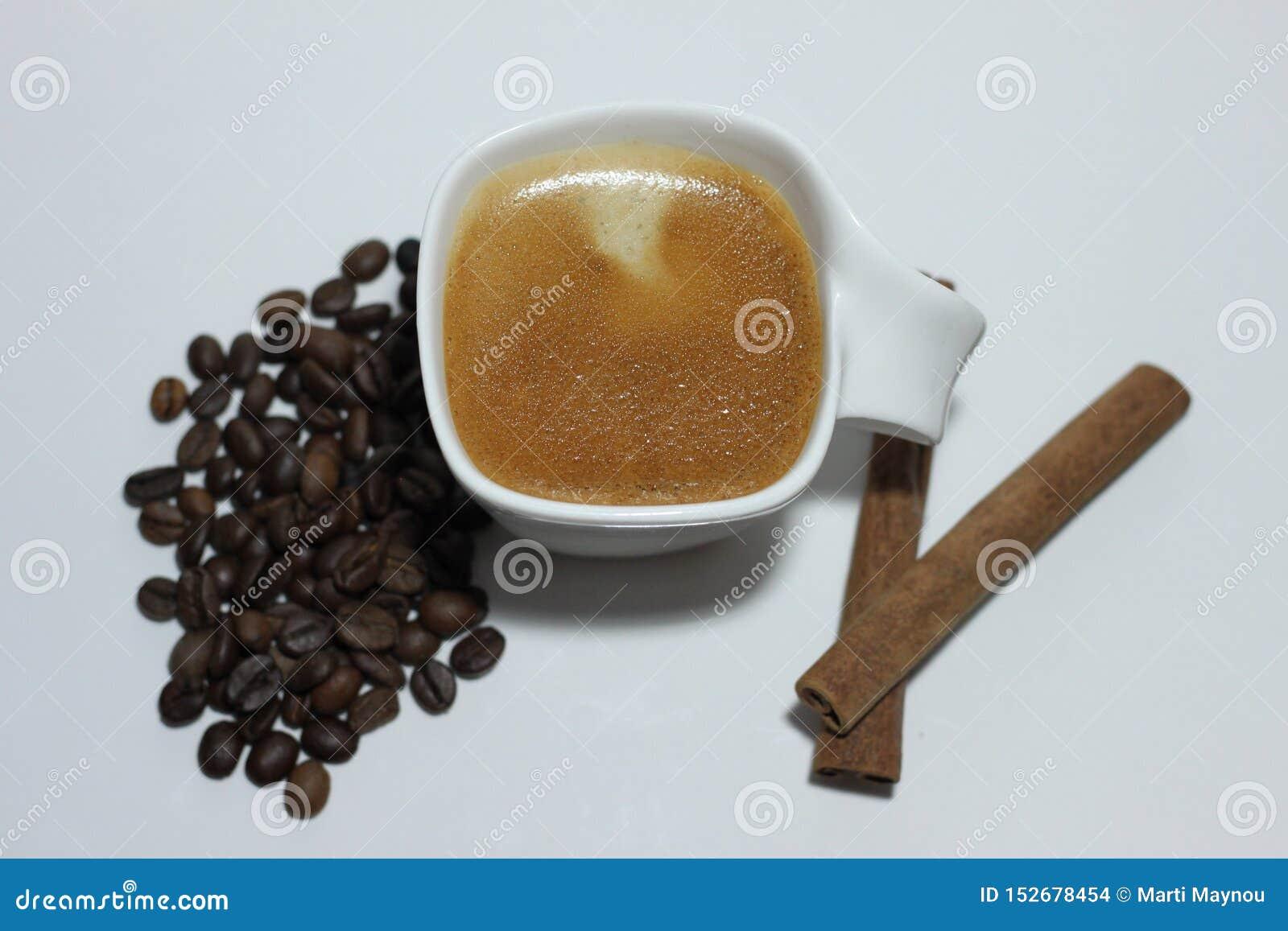 Tasse Kaffee, Bohnen und zwei Zimtstangen