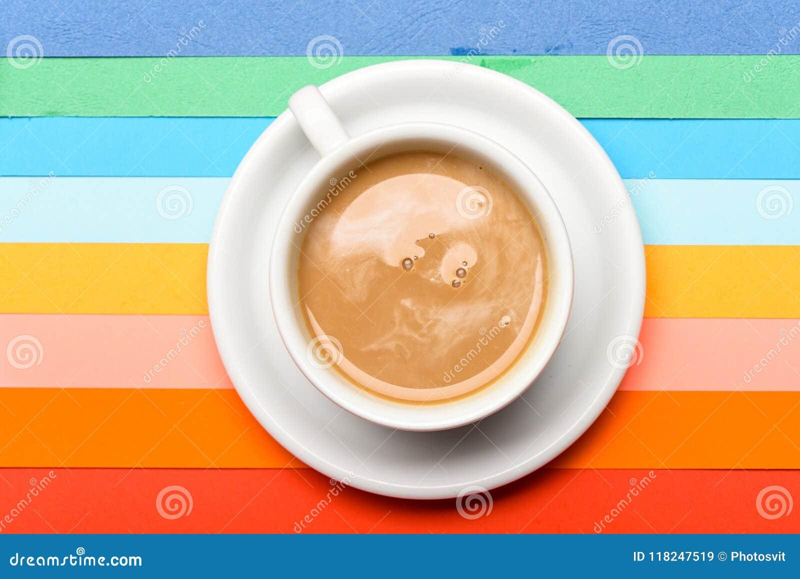 Tasse Kaffee mit Milch- oder Cappuccinogetränk auf buntem als Regenbogenhintergrund Dosis des Energiekonzeptes Kaffee an
