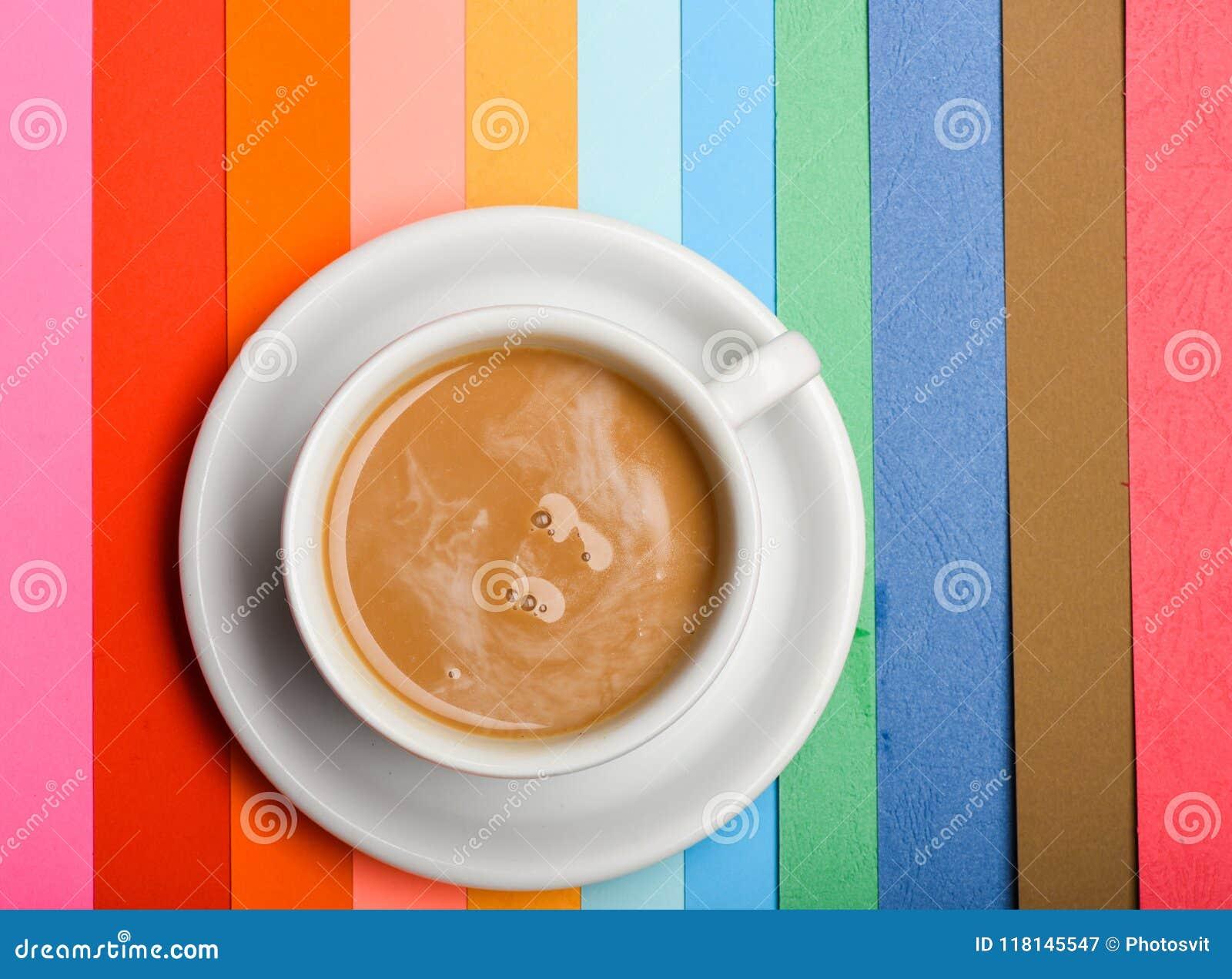 Tasse Kaffee mit Milch- oder Cappuccinogetränk auf buntem als Regenbogenhintergrund Dosis des Energiekonzeptes Getränk mit