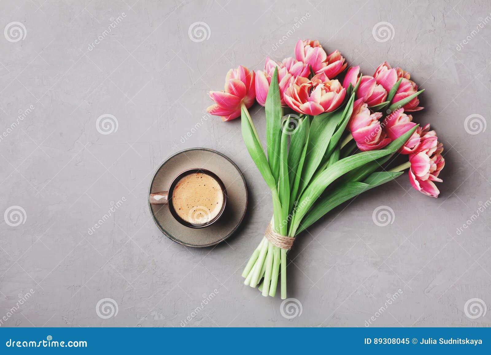 Tasse Kaffee mit schönen rosa Blumen für guten Morgen auf grauer Steintischplatteansicht in Ebene legen Art Frühstück am Mutterta