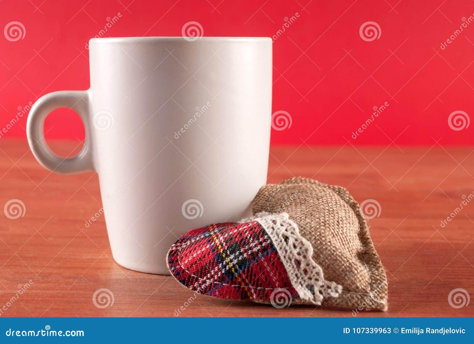 Tasse Kaffee und Herd auf hölzernem Schreibtisch und rotem Hintergrund