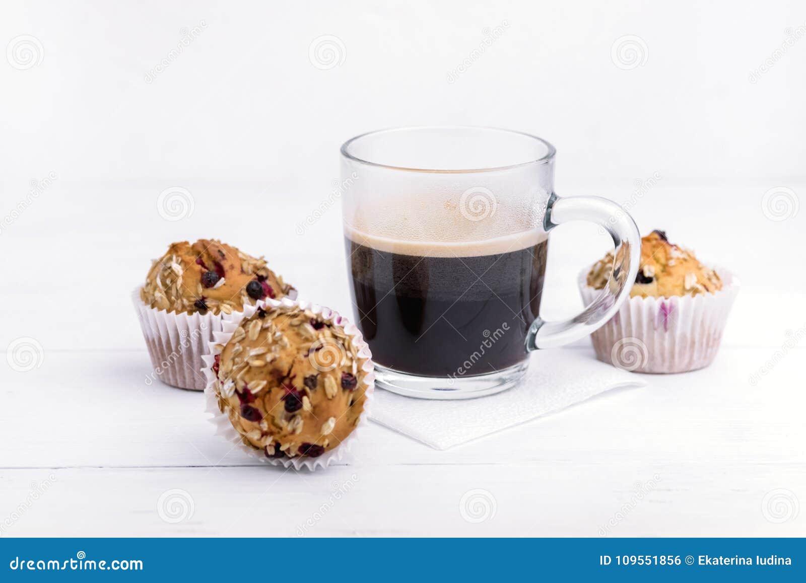 Tasse Kaffee und Muffins mit den Moosbeeren geschmackvoll und schönem Weiß-Hintergrund der kleinen Kuchen