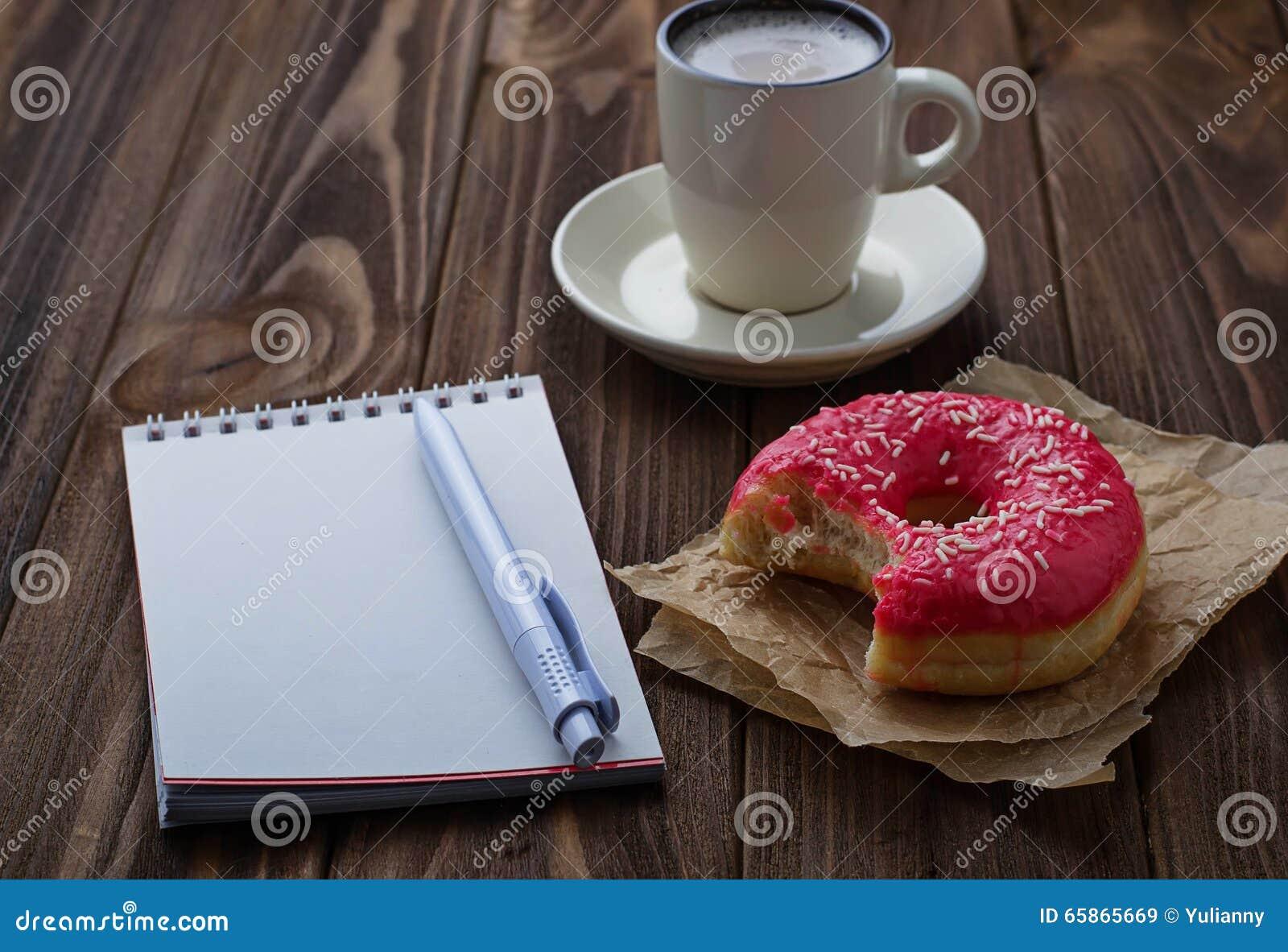 Tasse mordue de beignet de café et de carnet