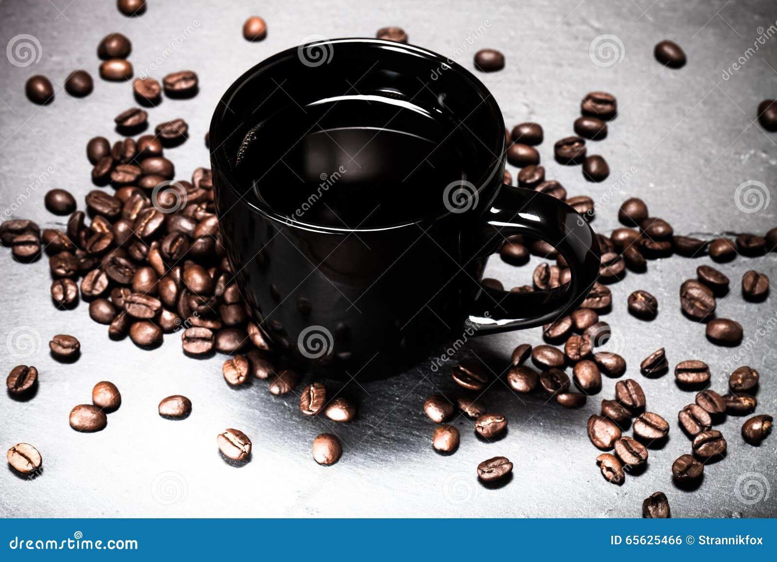 Tasse noire de café et de graines de café sur le fond d ardoise À