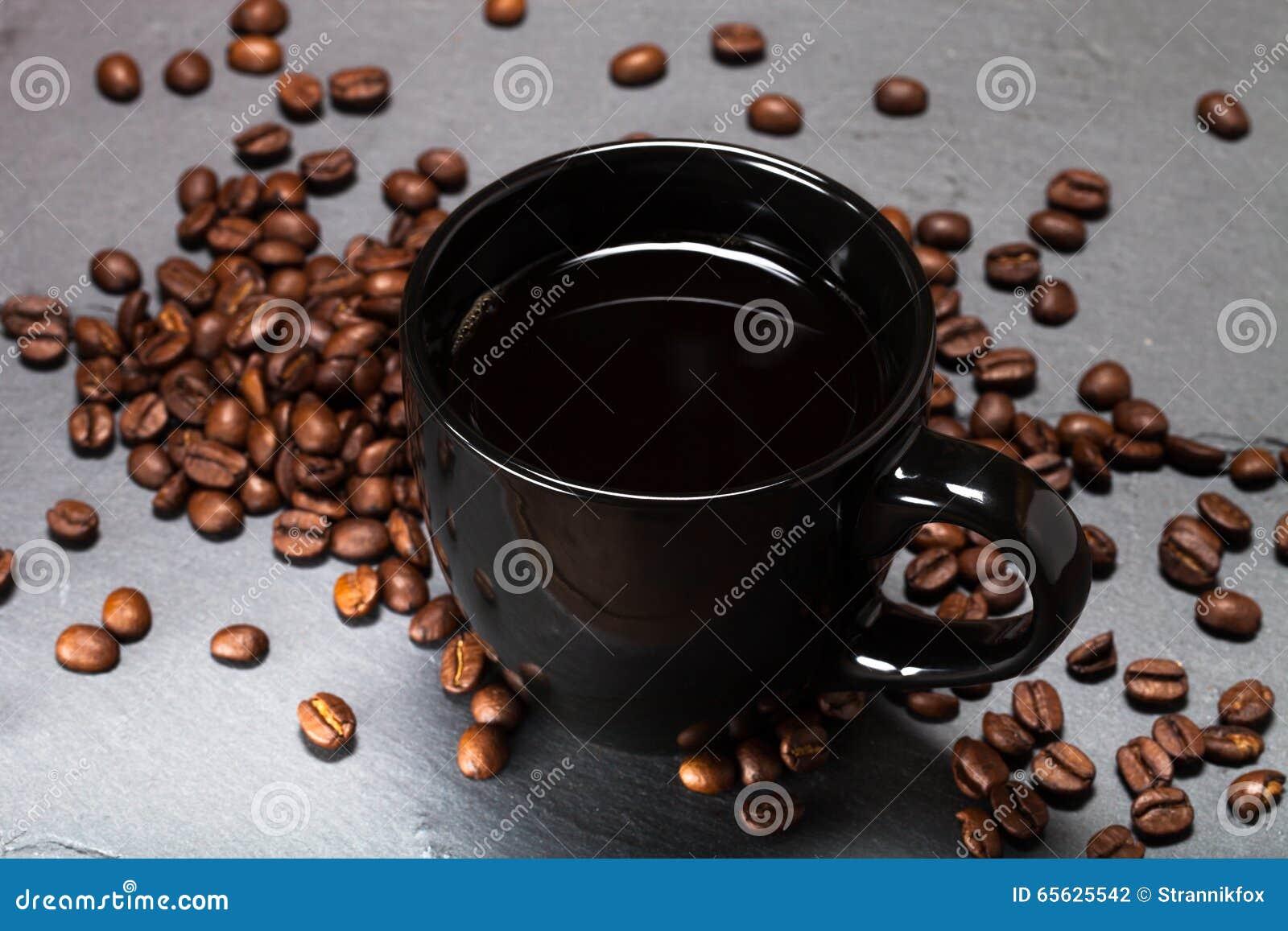 Tasse noire de café et de graines de café sur le fond d ardoise