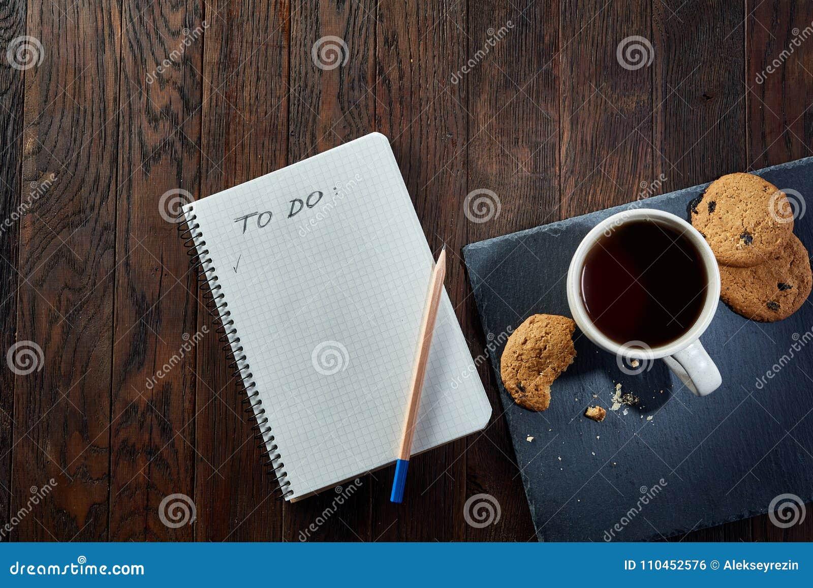 Tasse Tee mit Plätzchen, Arbeitsbuch und einem Bleistift auf einem hölzernen Hintergrund, Draufsicht