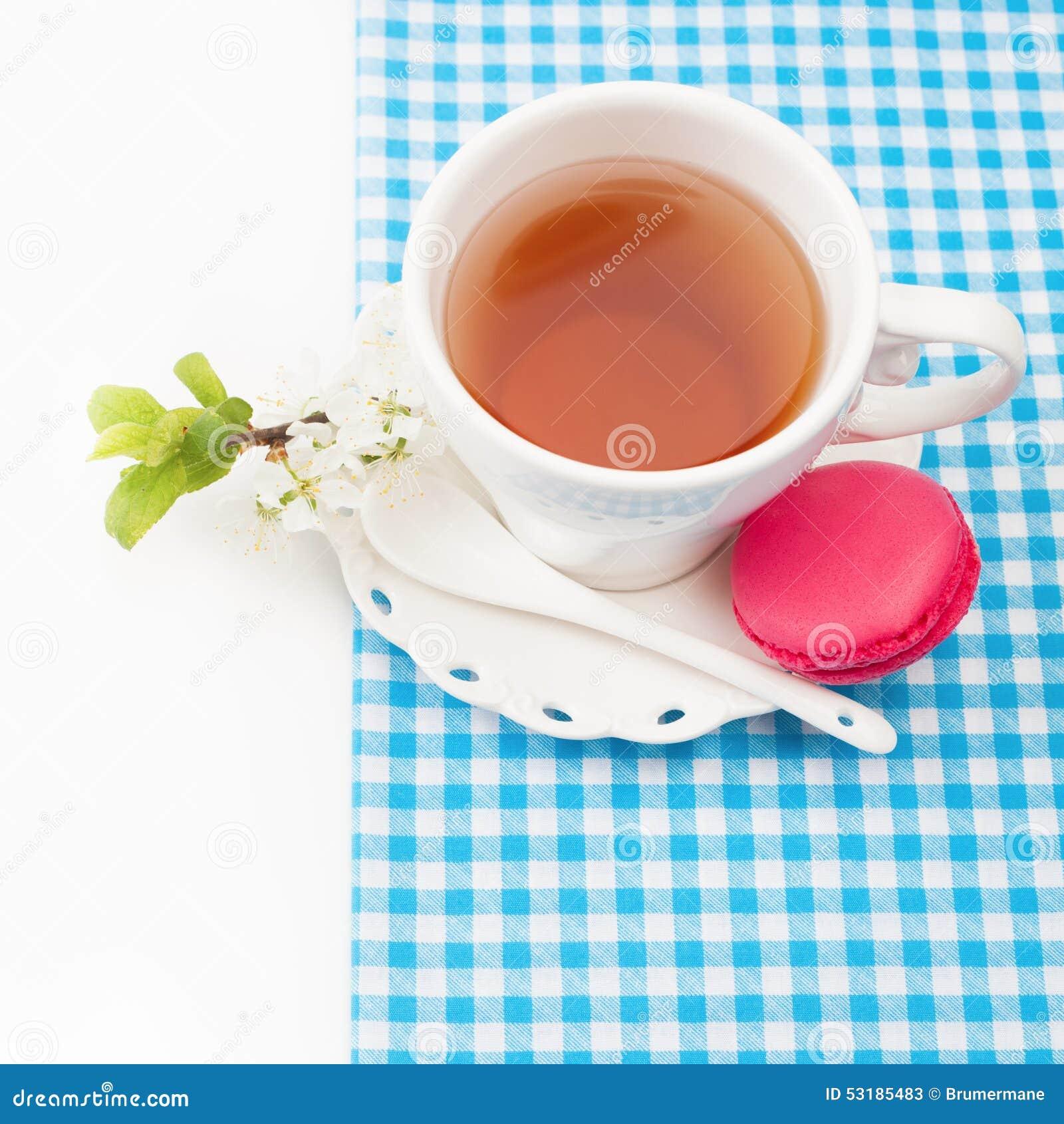 Tasse Tee und süße und bunte französische Makrone und eine Kirsche
