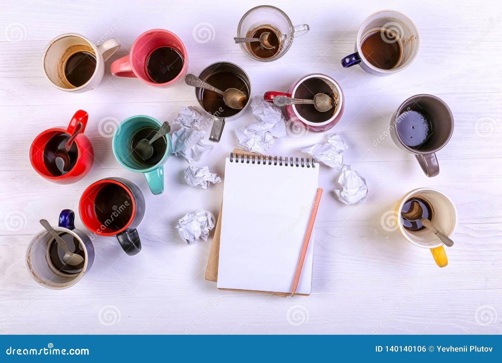 Tasses de café sales vides, différentes couleurs sur la table et un carnet pour écrire une lettre Dopant de caféine de concept, m