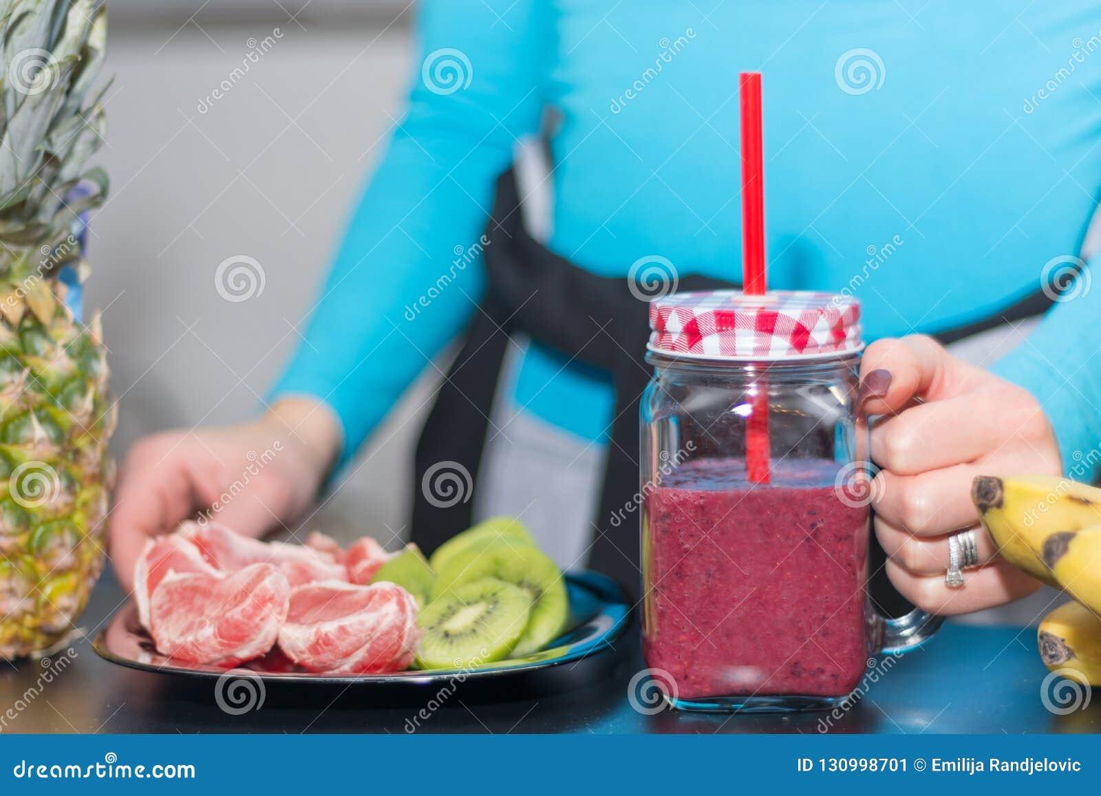 Tasses de pot de maçon de participation de fille remplies de smoothie rouge