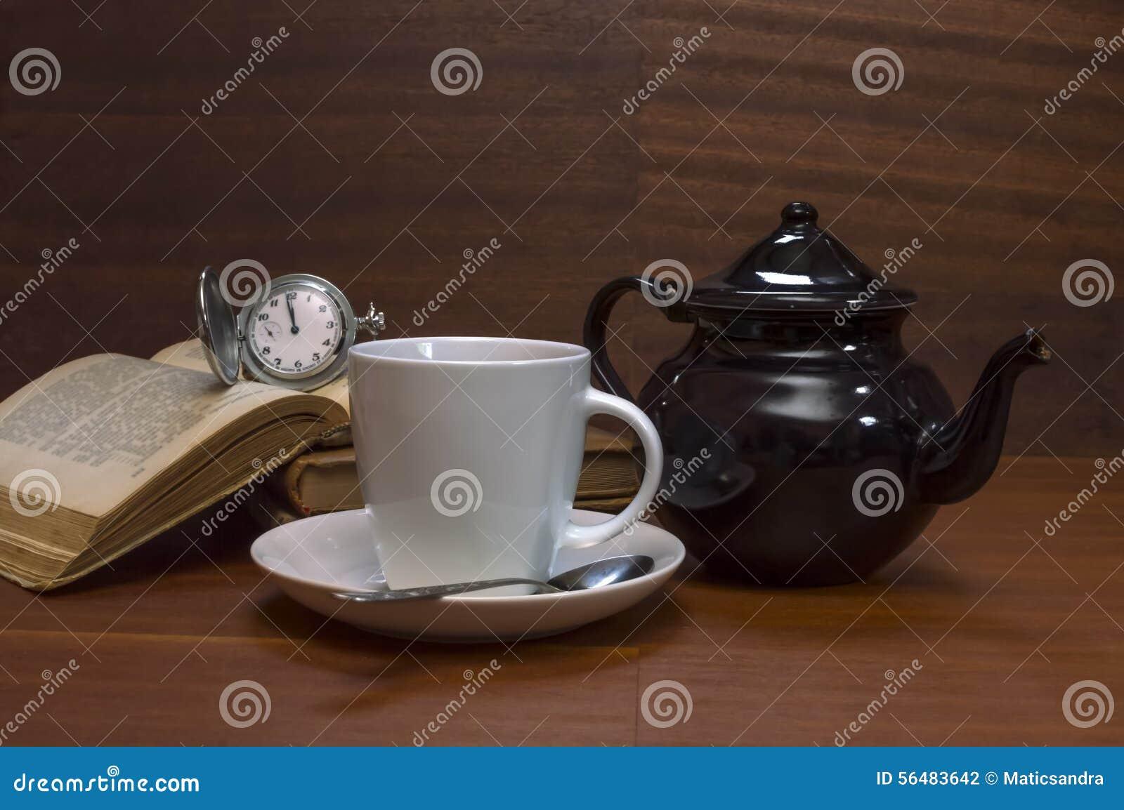 Tasses de thé avec la théière, les livres et la vieille montre de poche sur la table en bois