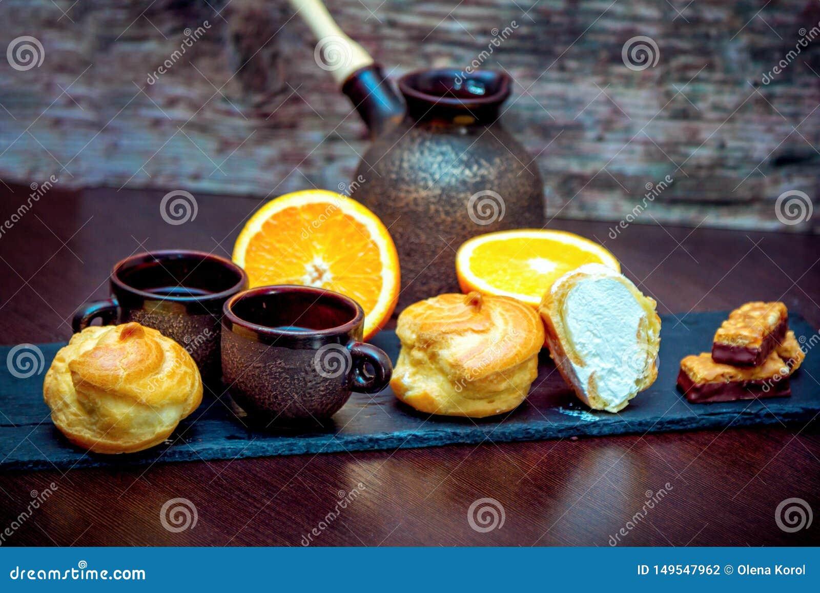 Tasses en céramique de style de cru, pot de brassage de café, orange et biscuits frais et sucreries de chocolat avec les abricots