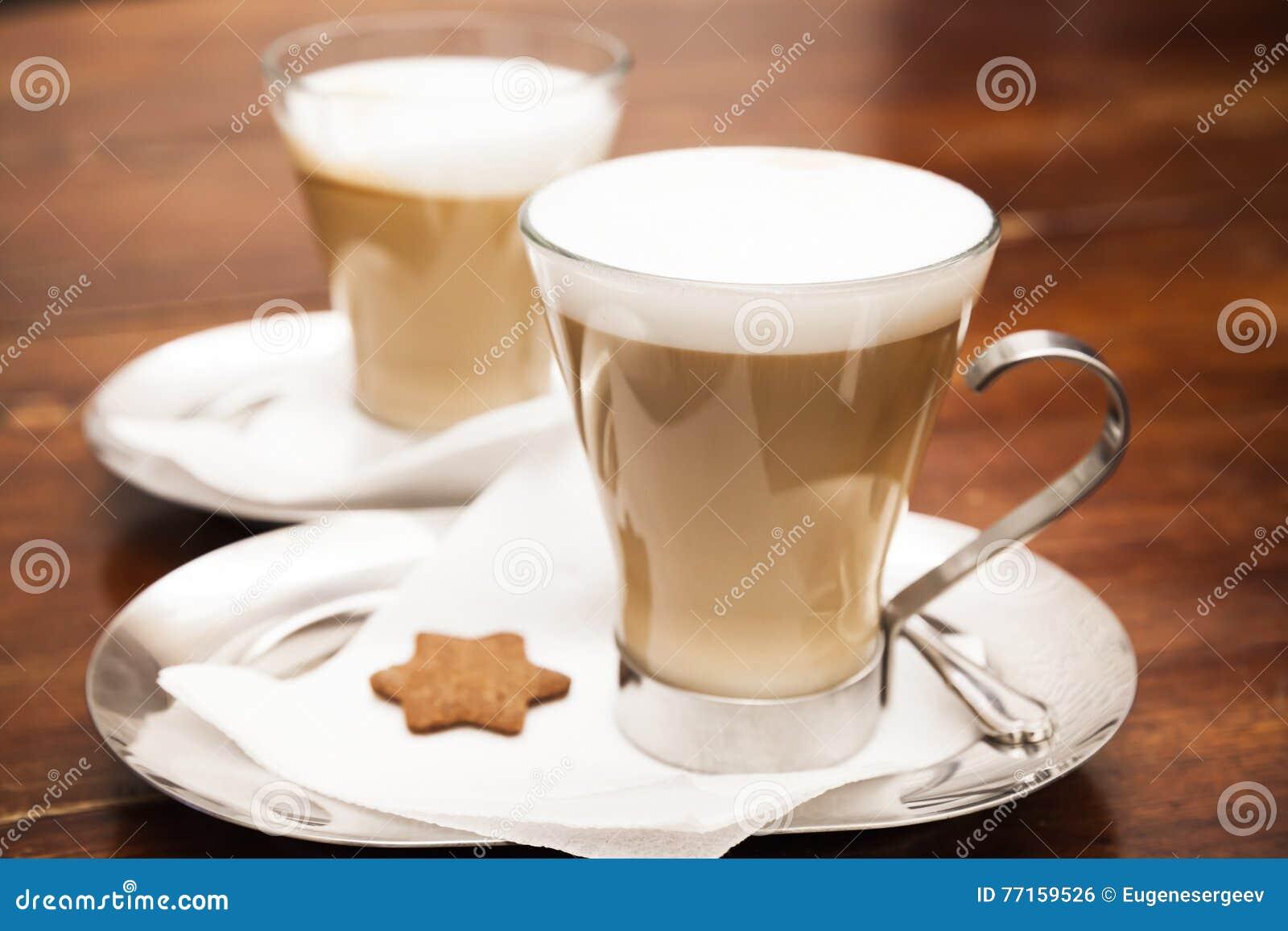 Tasses en verre complètement de cappuccino sur la table en bois