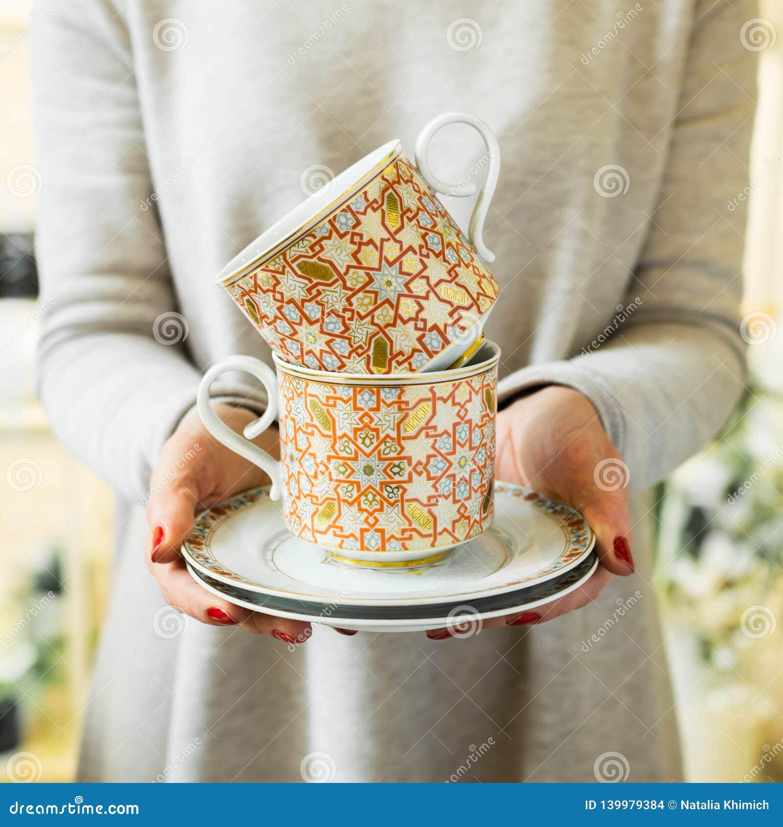 Tasses et soucoupes élégantes de thé ou de café chez les mains des femmes La femme tient un plat en céramique