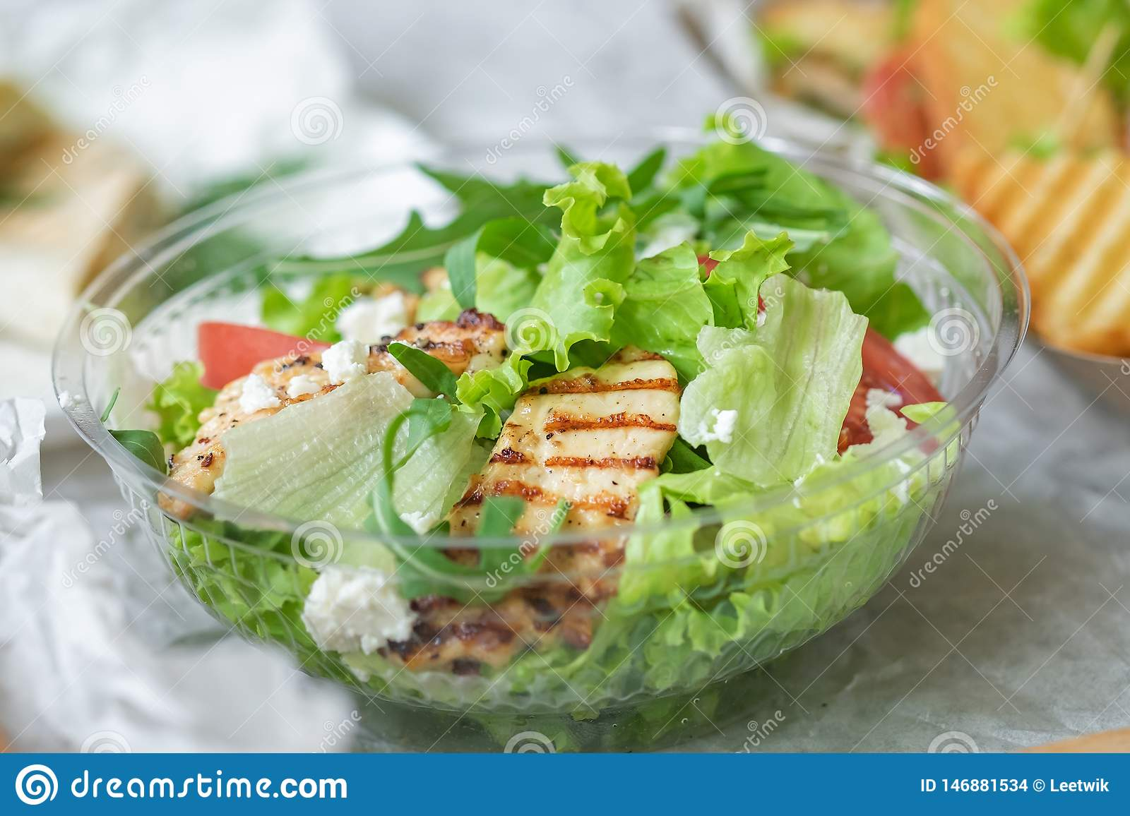 Tasty appetizing fresh salad with chicken, tomatoes, cucumbers and cheese parmesan in bowl. Close-up