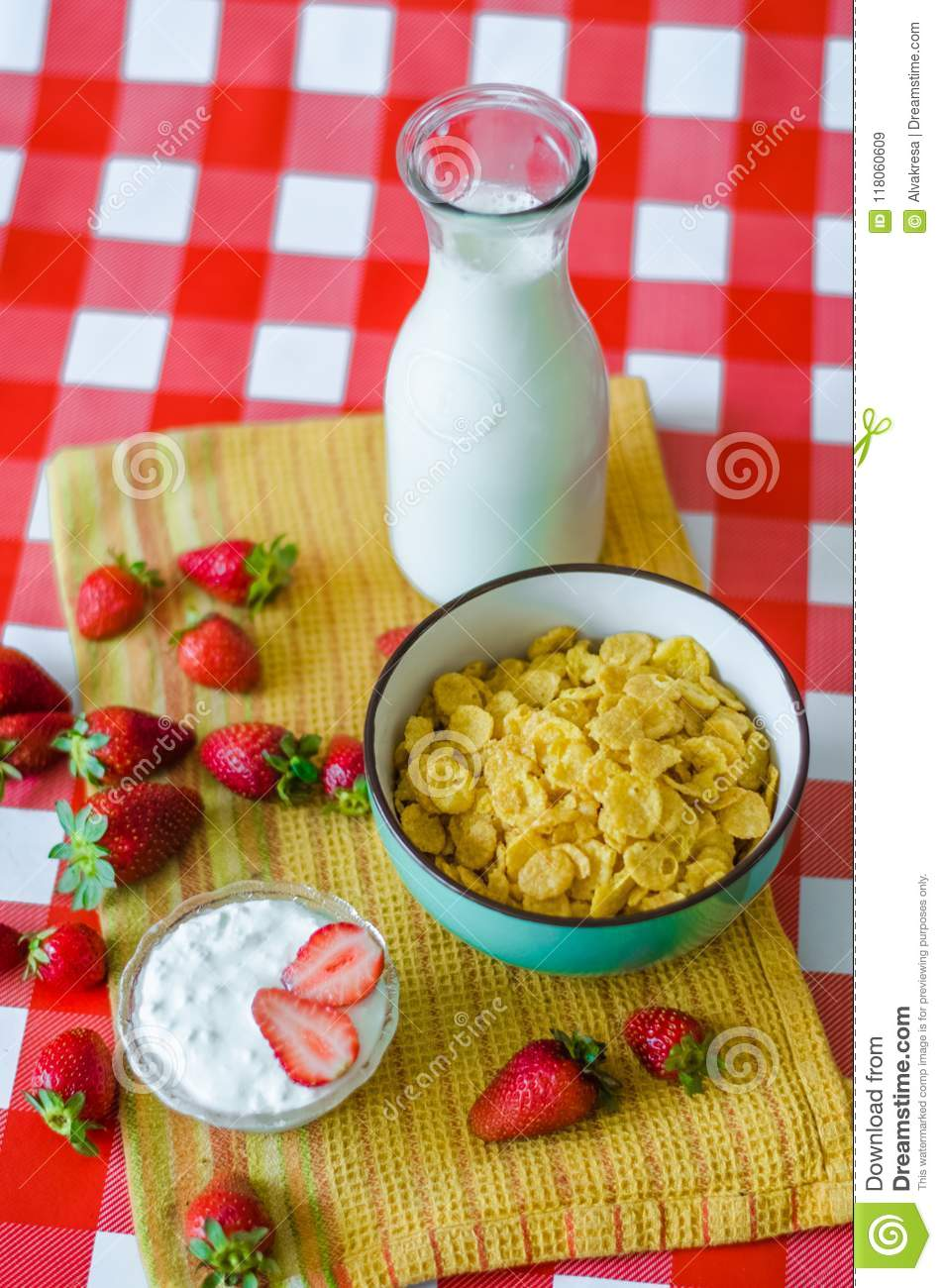 Tasty breakfast, fresh milk in glass bottle, cereals with honey and nuts in green ceramic bowl, tasty yogurt in small glass bowl