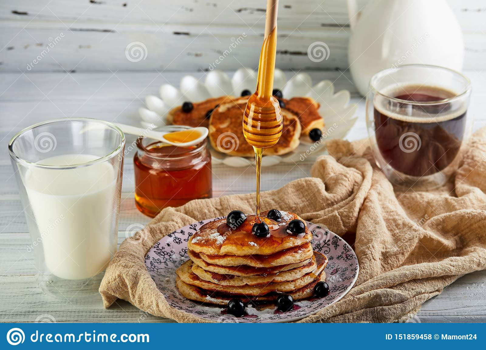 Tasty breakfast. A stack of pancakes with honey syrup a glass of milk, espresso coffee and honey on a wooden white