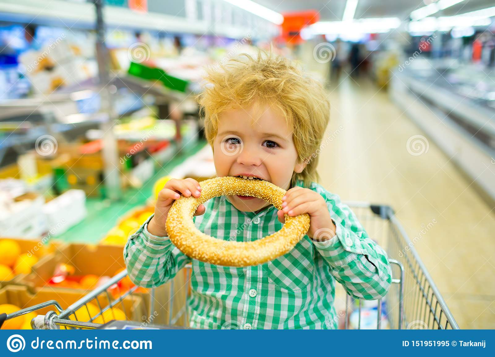 Tasty bun. Boy bites bagel with sesame in the supermarket. Bakery products. Shopping Shopping for food. Child food