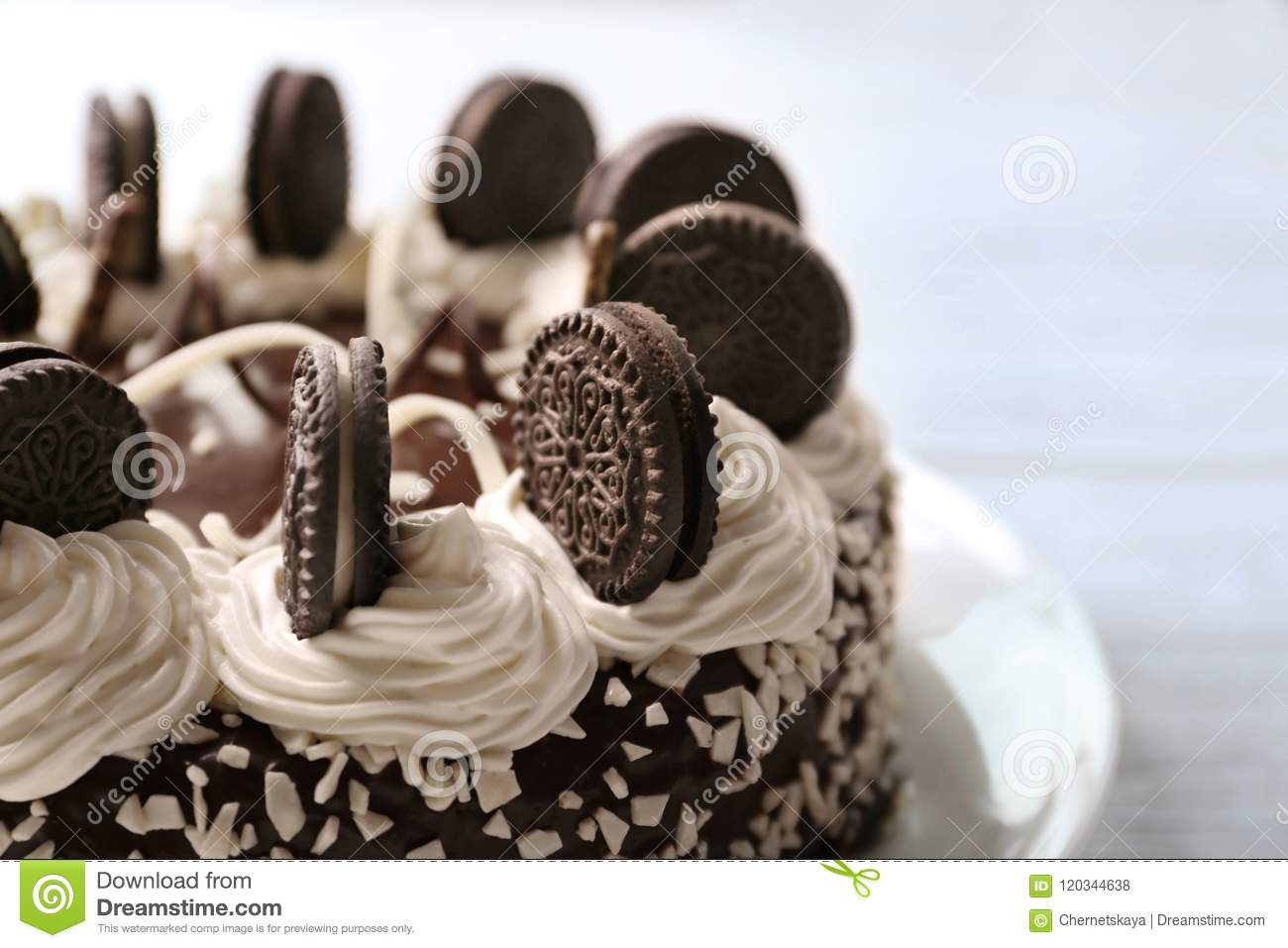 Delicious Cake With Chocolate Cookies And Cream On Blurred Background Close Up View