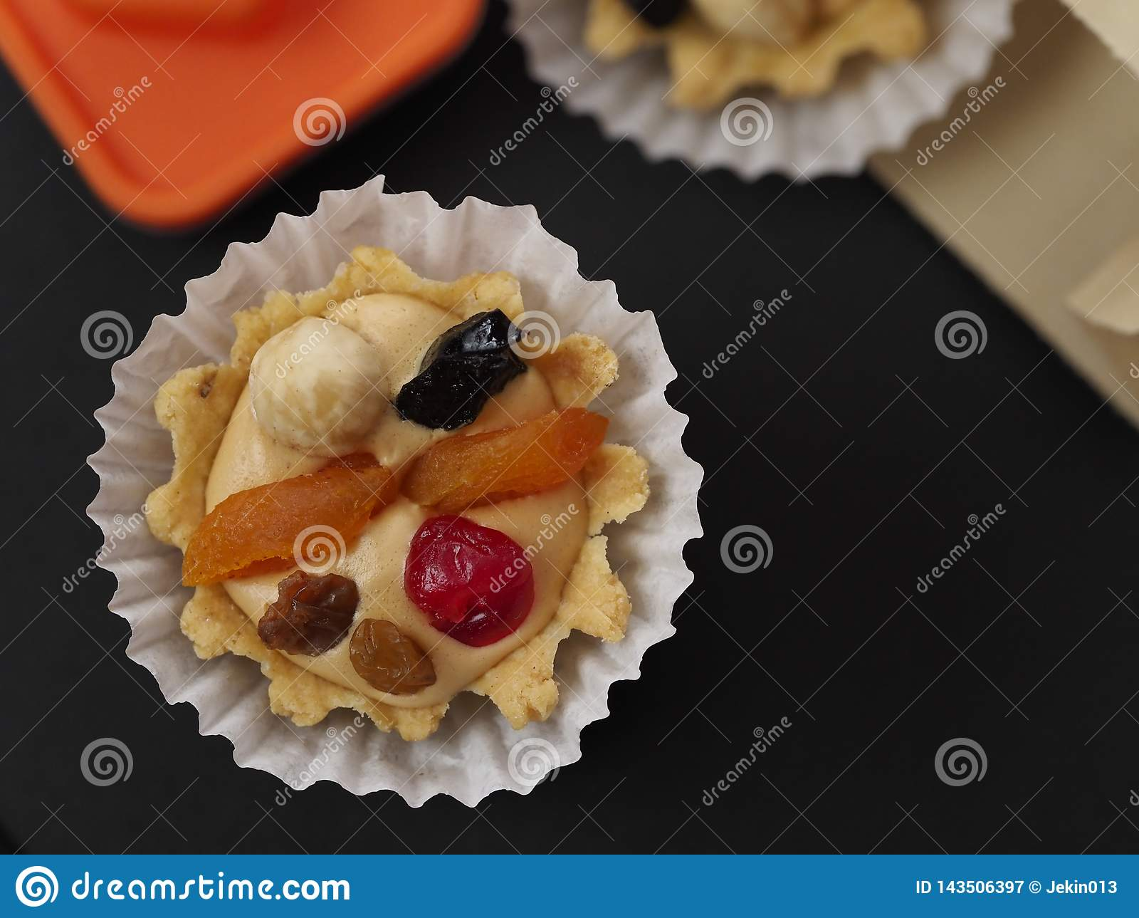 Two sand air cream, berries and nuts cakes and orange figure