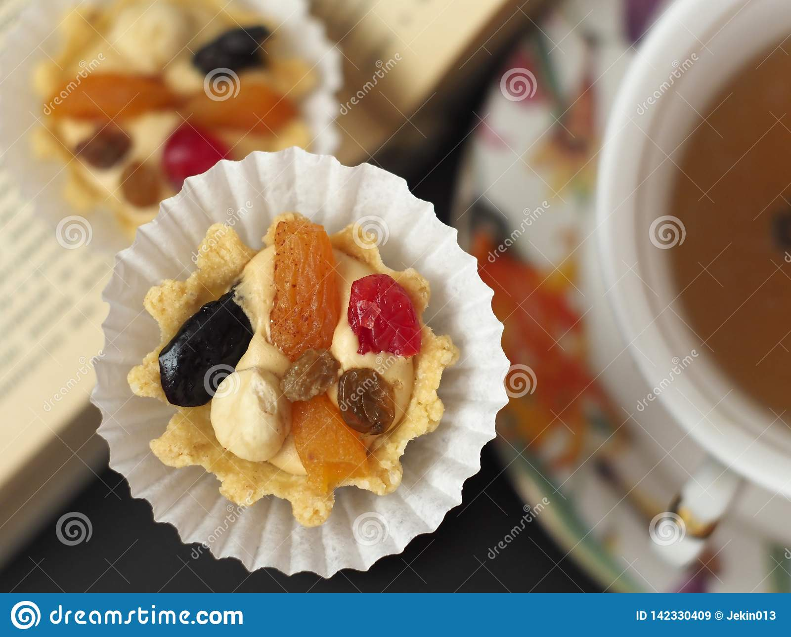Two cakes with butter cream and fruit near a cup of tea at the opened book