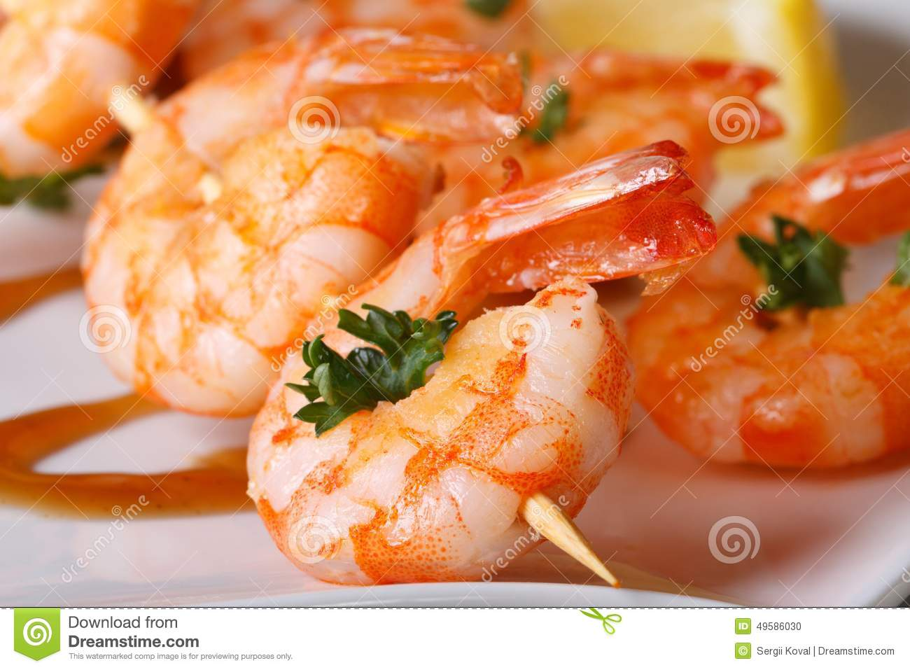 Tasty grilled shrimp on wooden skewers macro with sauce