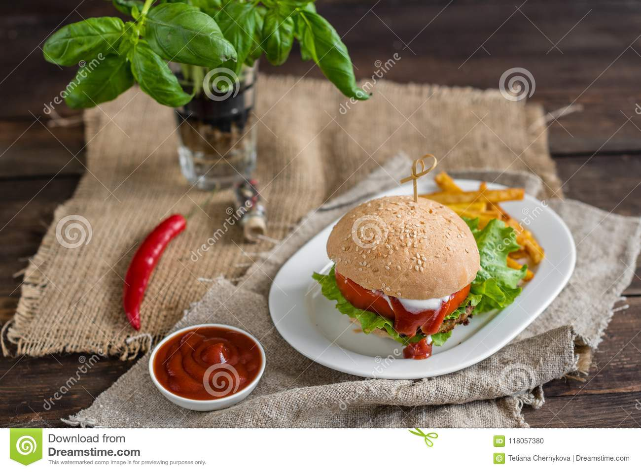 Tasty hamburger with meat and vegetables against a dark background