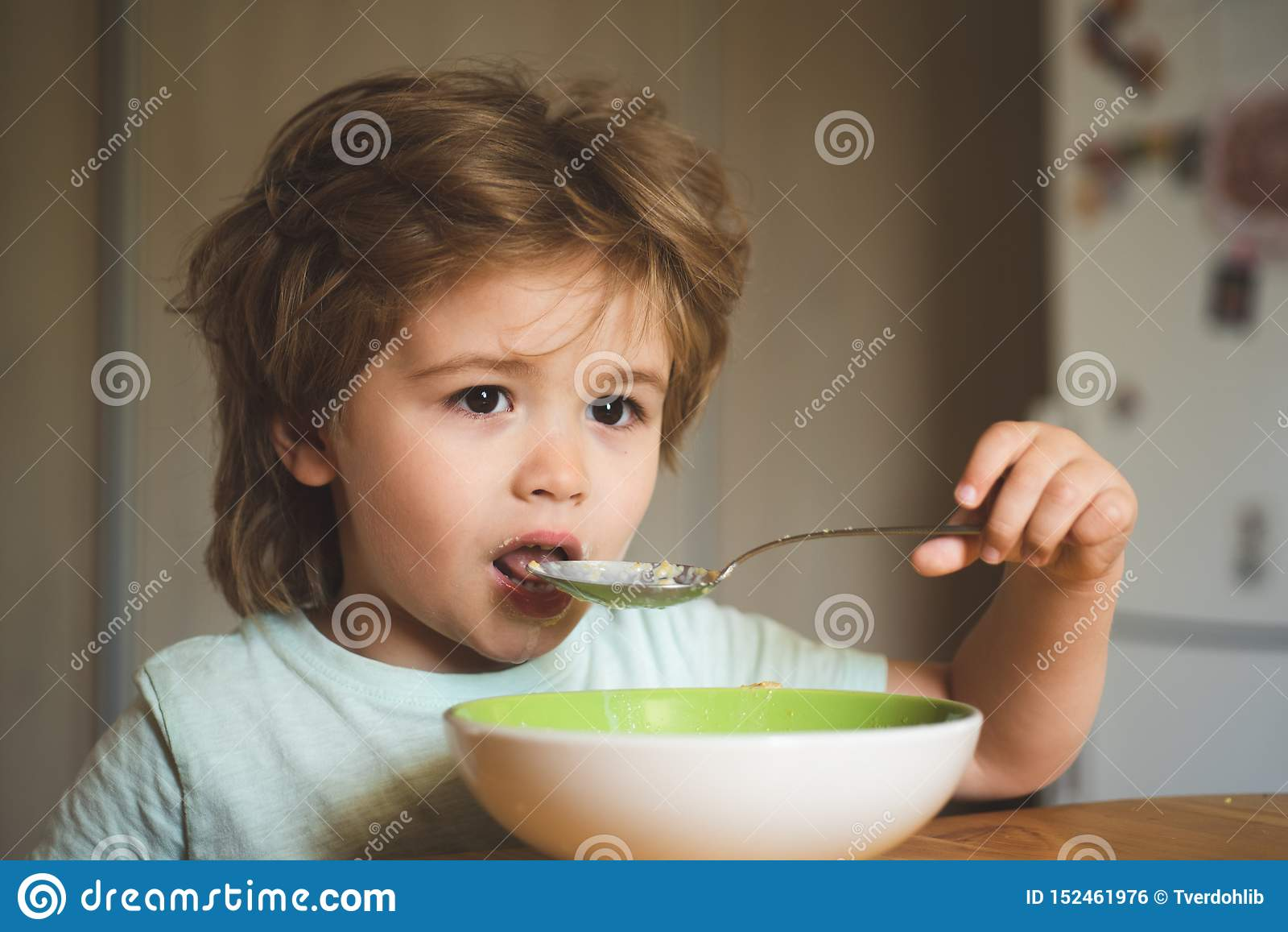 Tasty kids breakfast. Cute child eating breakfast at home. Baby eating. Good morning in Happy family. Hungry little boy