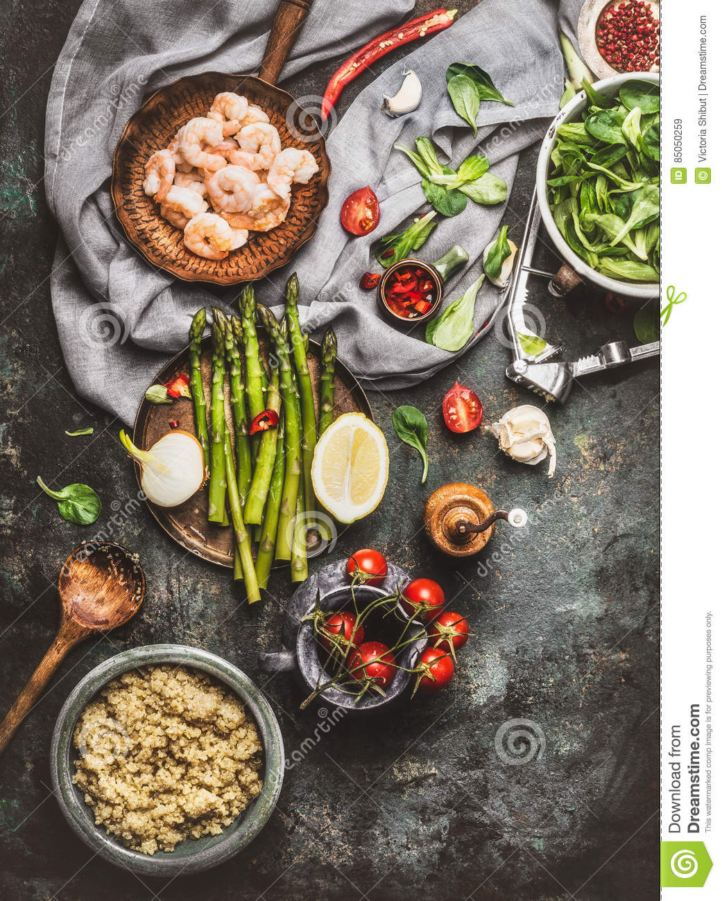 Tasty quinoa salad preparation with wooden spoon , Shrimps , asparagus and various healthy vegetables on rustic kitchen table bac