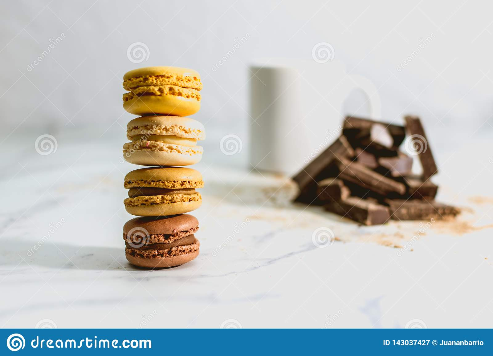 Tasty sweet macarons with cup of coffee on background